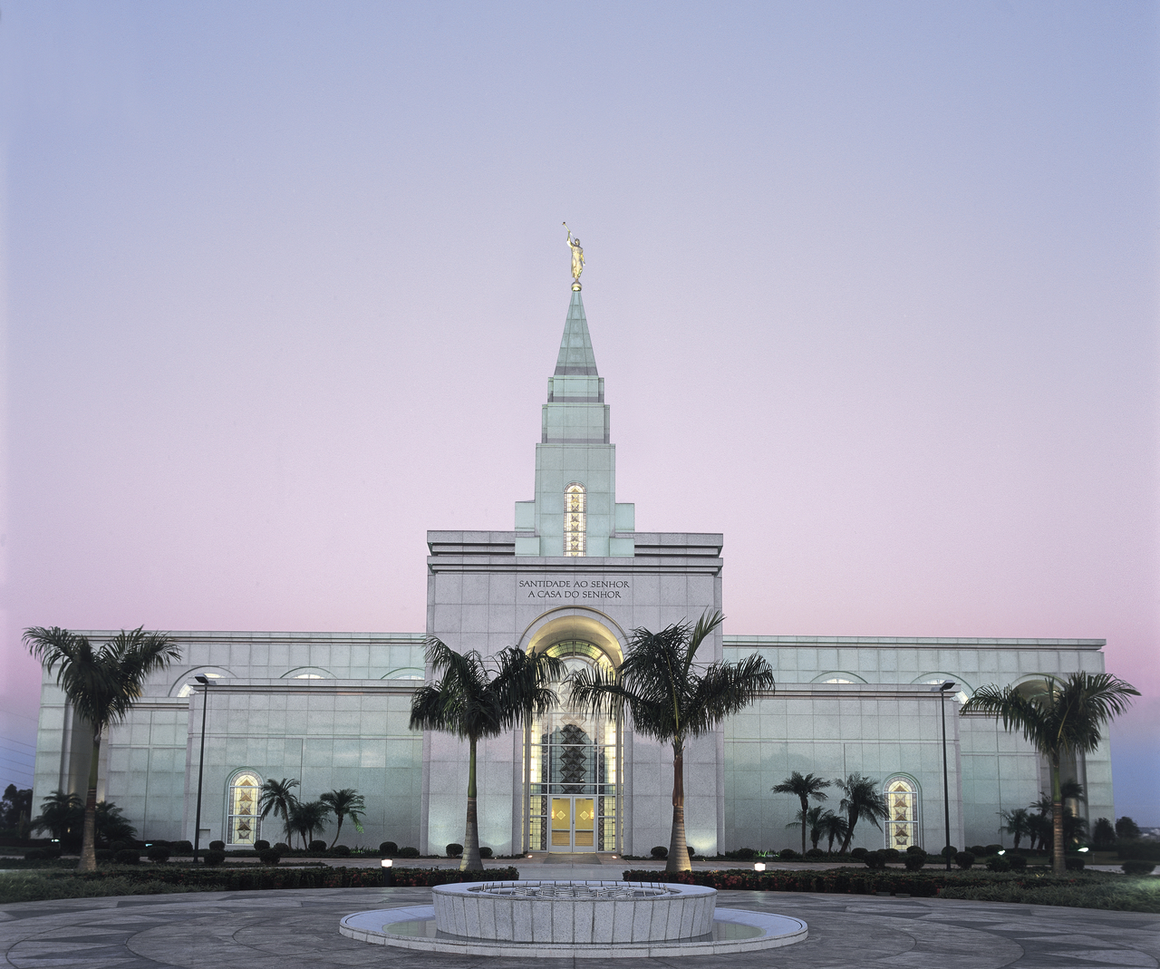The Campinas Brazil Temple lit up in the early evening, with palm trees near the entrance.
