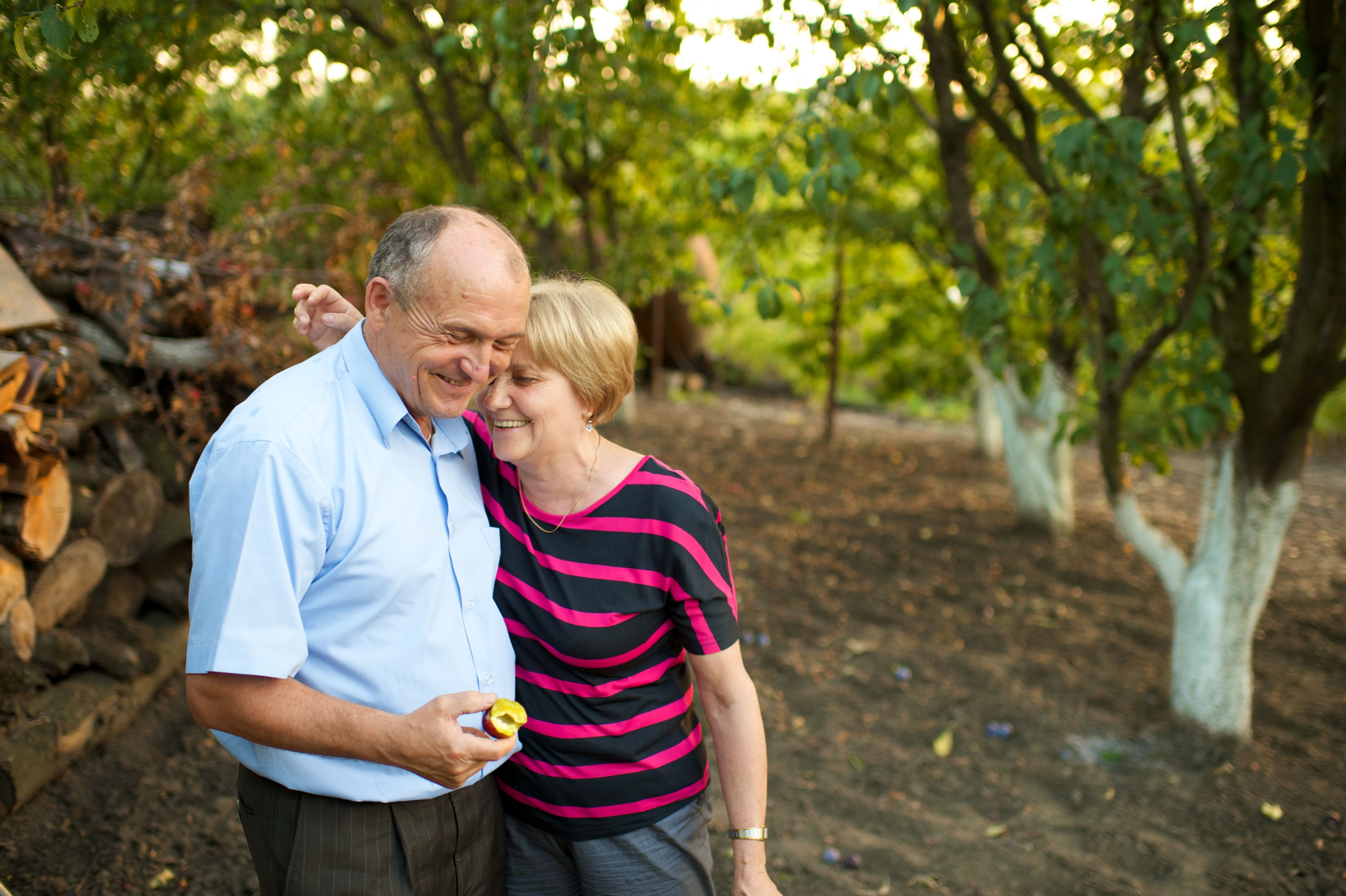An elderly couple standing in an orchard in Romania.