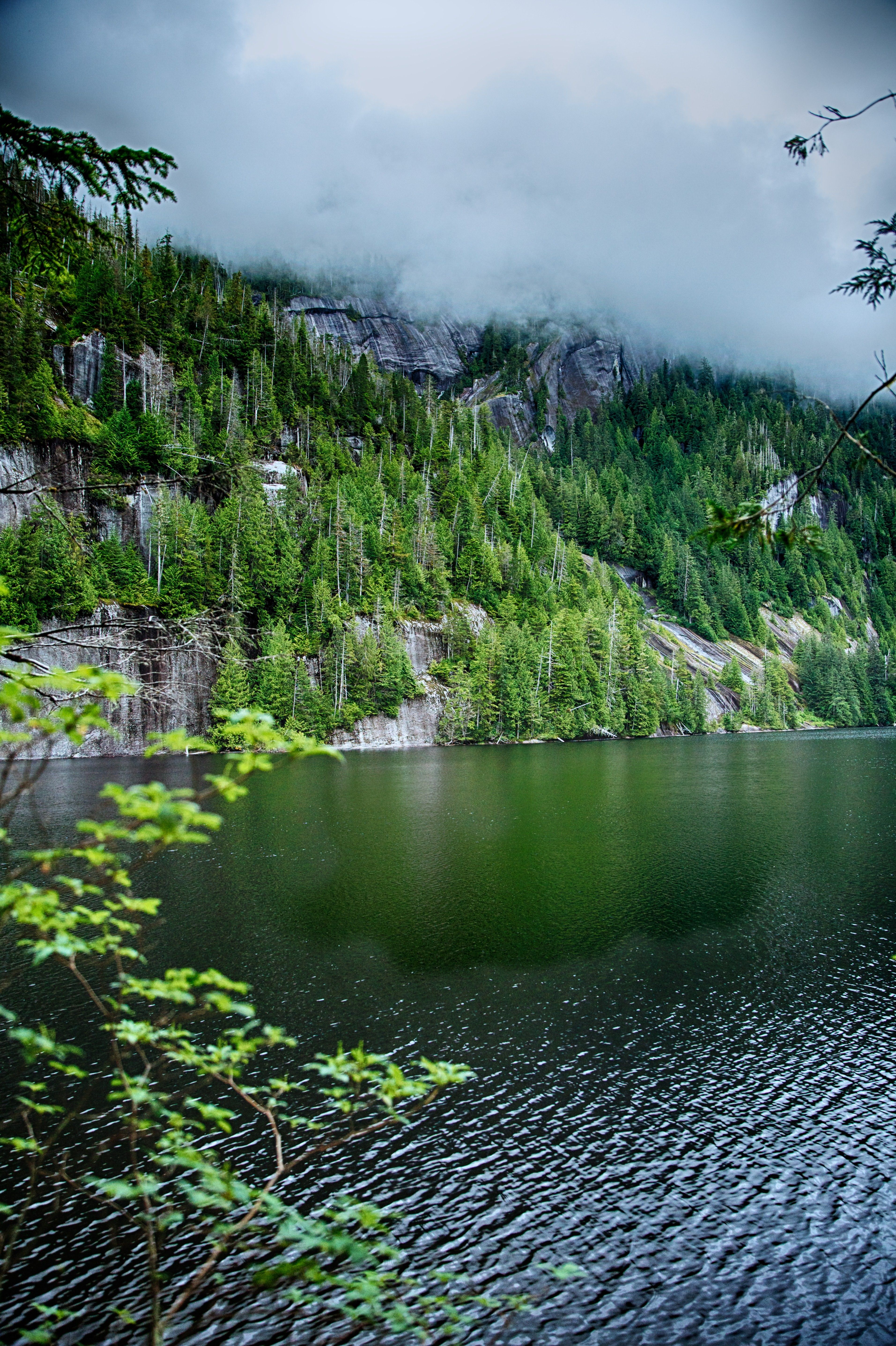 Fog lies low over mountains near a lake in Alaska.