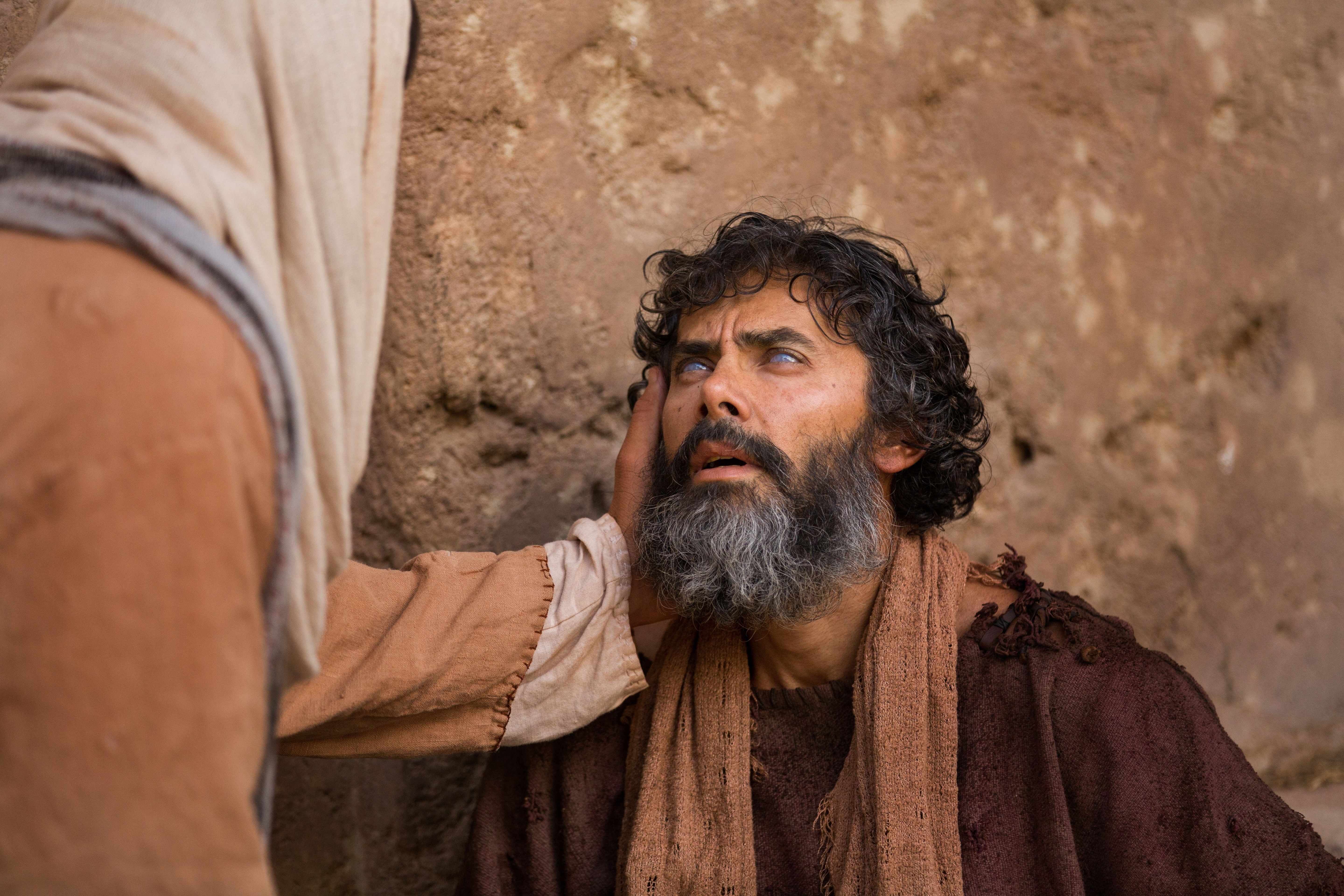 Christ talking with a blind man on the street.