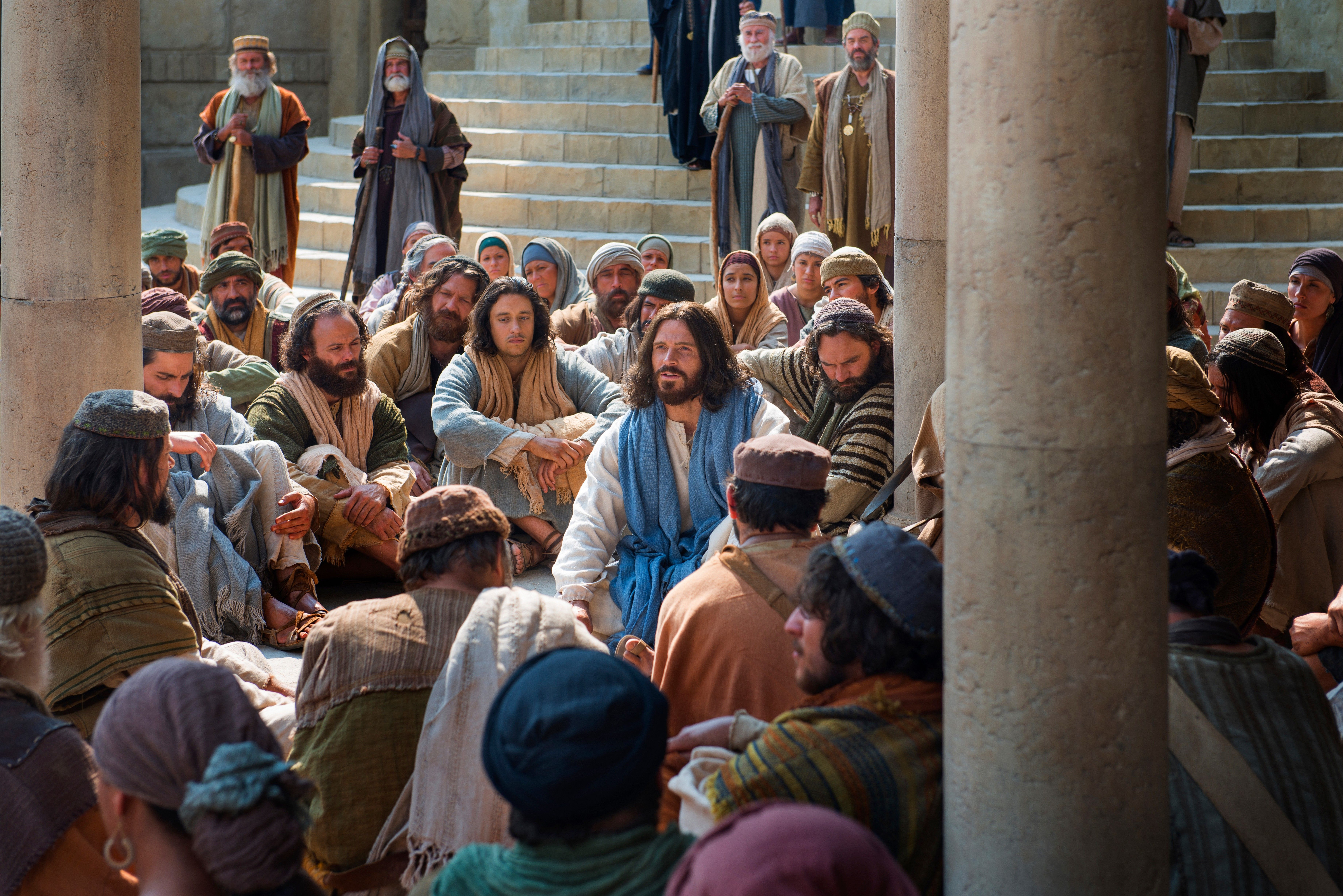 Jesus sits in the midst of a group of people and tells them of the greatest commandment.
