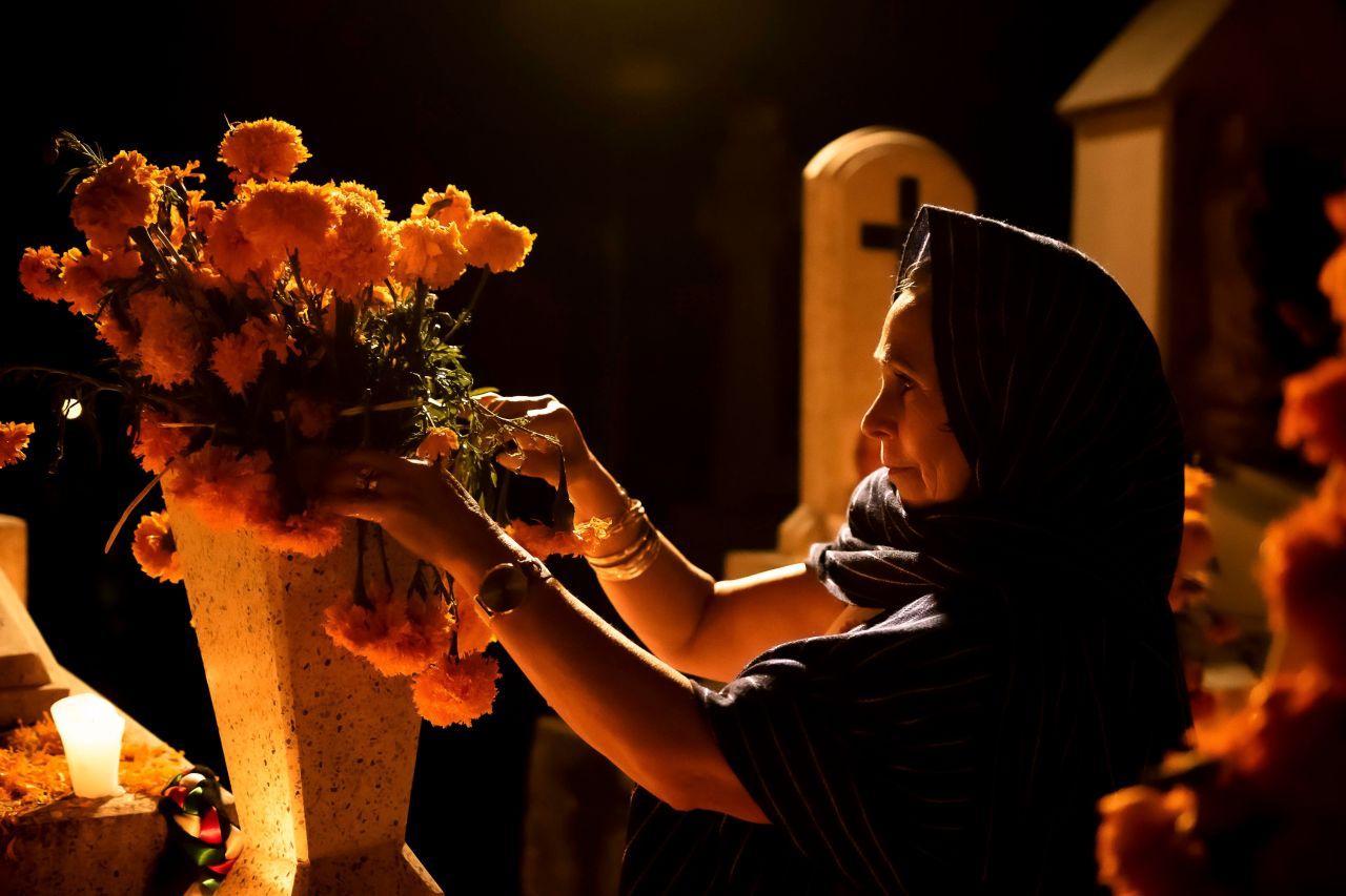 Una mujer arregla flores para el Día de los Muertos