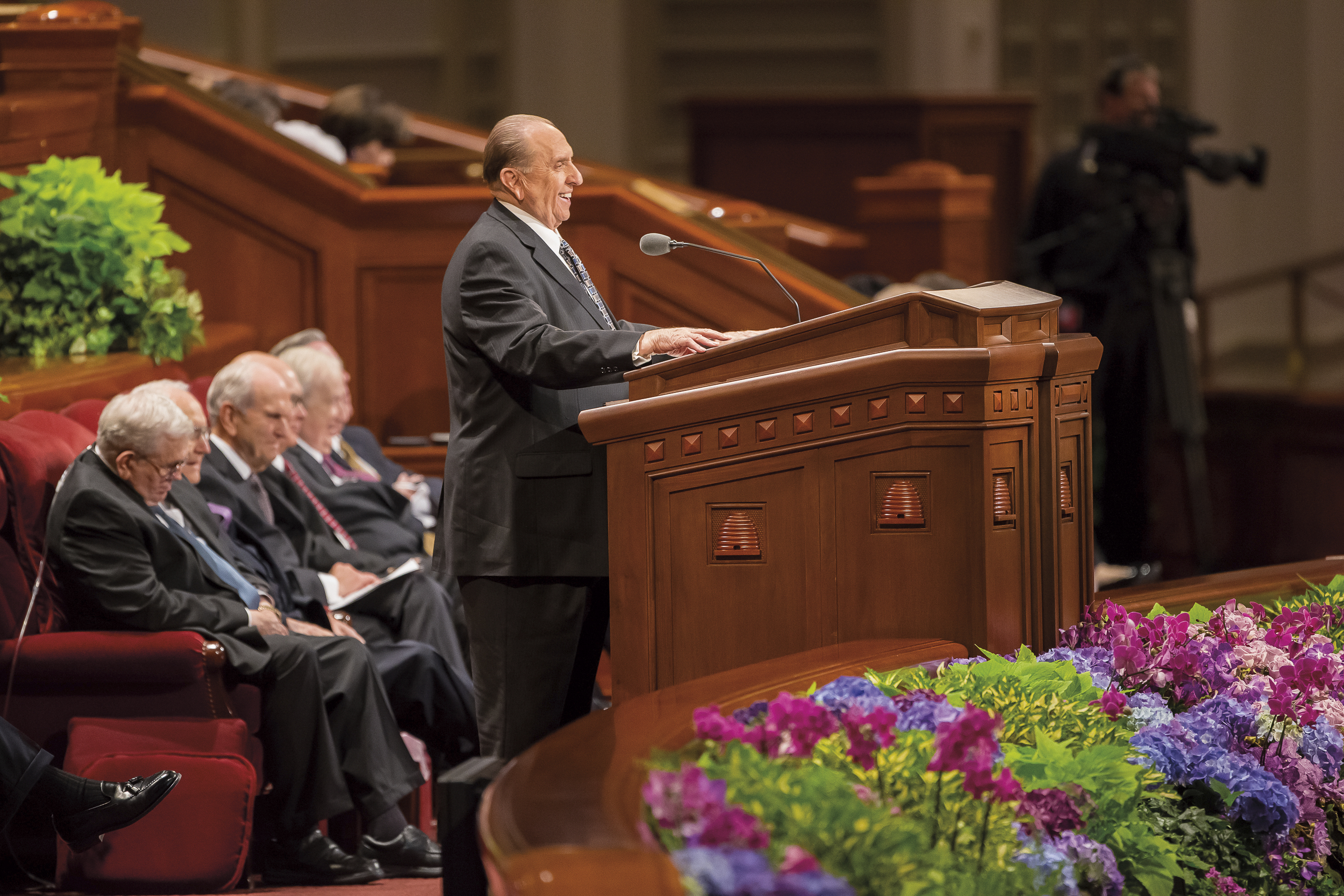 Thomas S. Monson standing at the pulpit at general conference, with several Apostles sitting behind him.