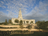 The entire San Antonio Texas Temple, with a view of the stairs leading to the entrance, the grounds, and trees and bushes lining the grounds.