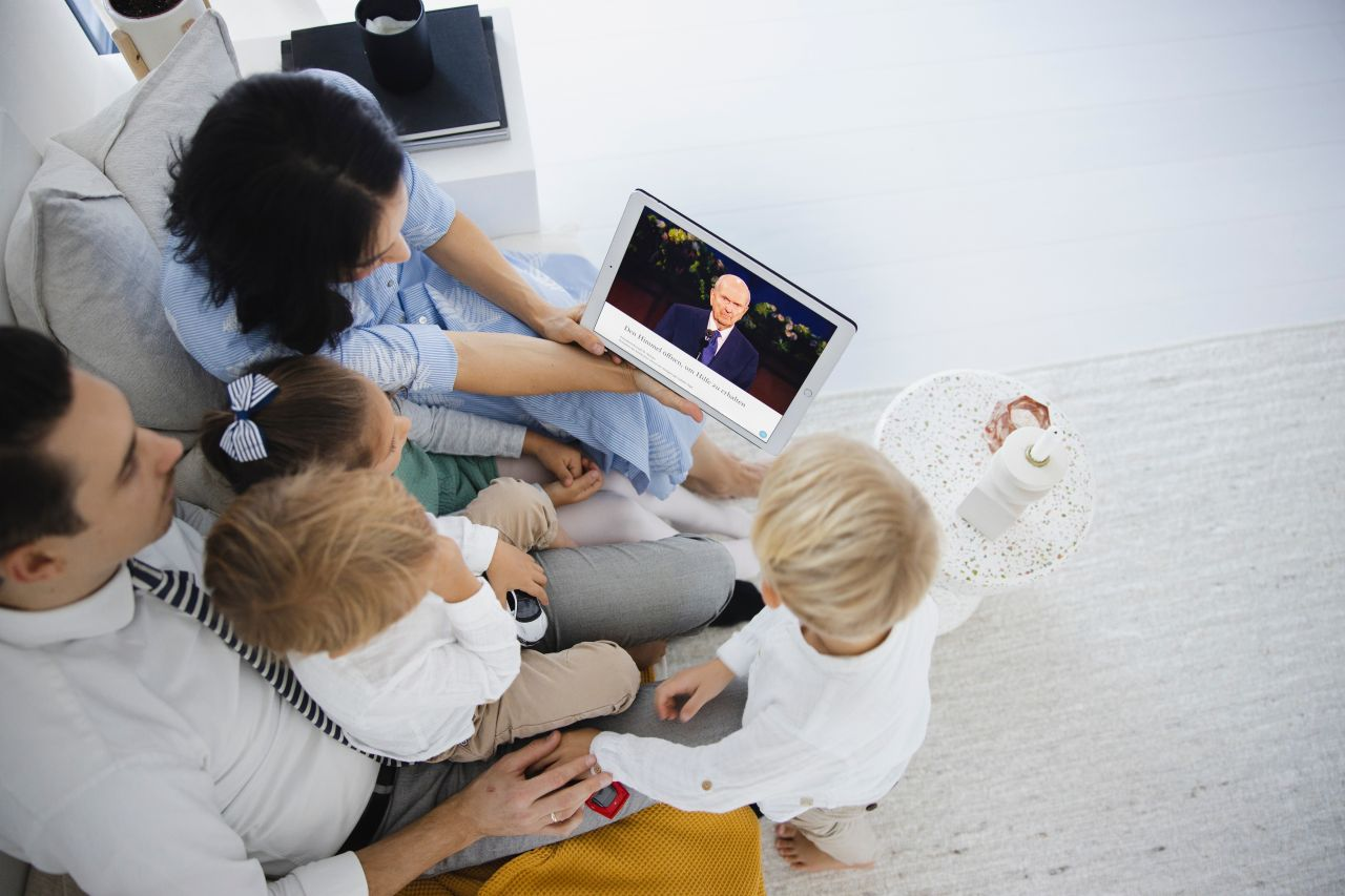 A family streams general conference on a tablet