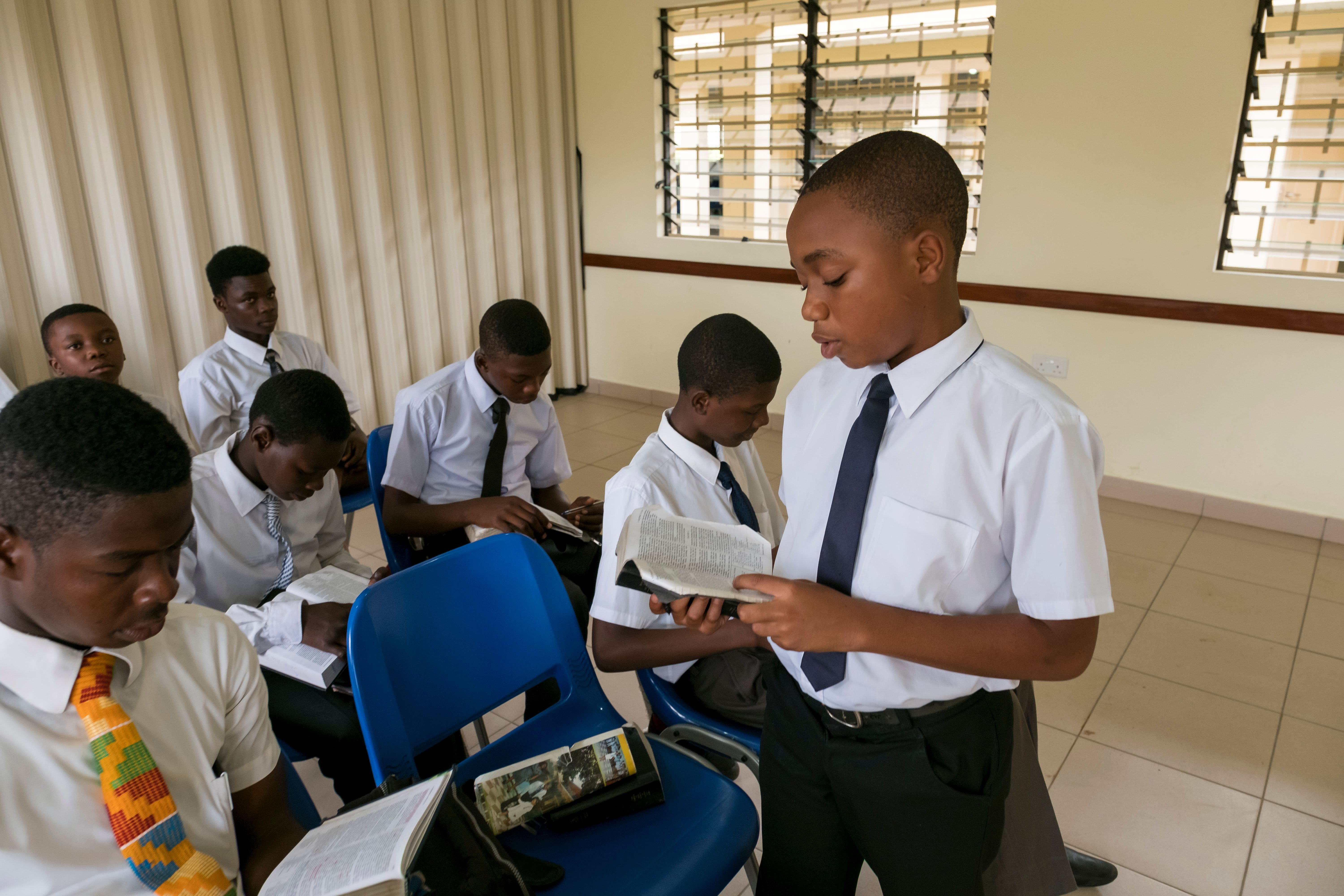 A group of young men sitting in a priesthood class in Ghana. One young man is standing and reading from the scriptures.