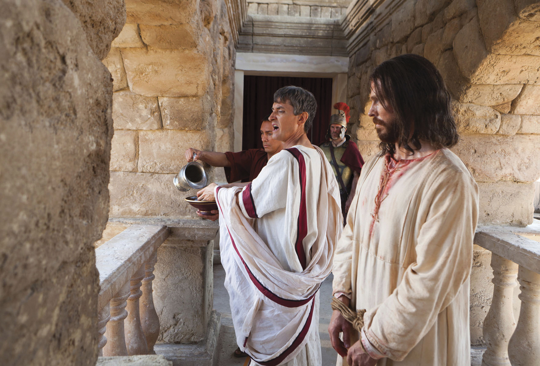 Pilate speaks to the people in the crowd and washes his hands of their accusations of Christ.