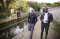 Cayo and Anthony walking alongside a waterway