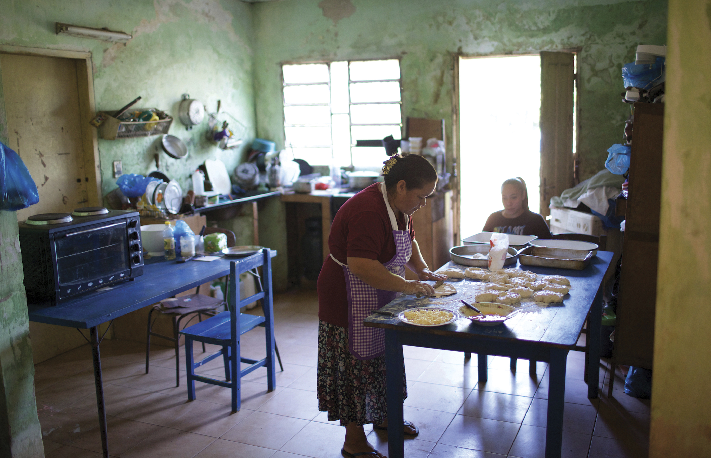 The day begins early for Adriana as she prepares dough for the bread she will bake and sell. All day long the kitchen table serves as a gathering place for the González family.