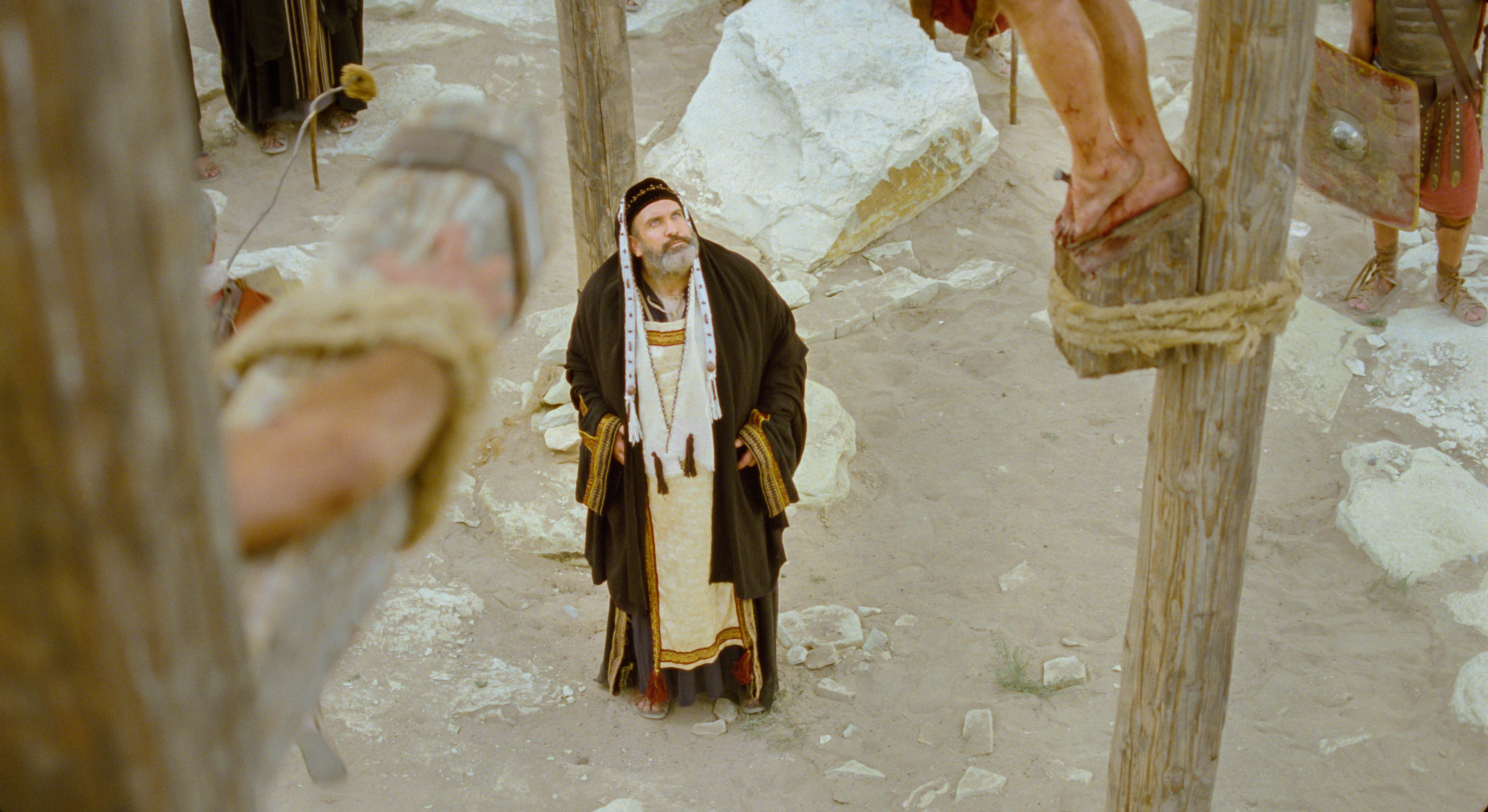 Caiaphas looks upon the Savior, who is hanging on the cross.