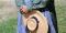 woman standing holding hat