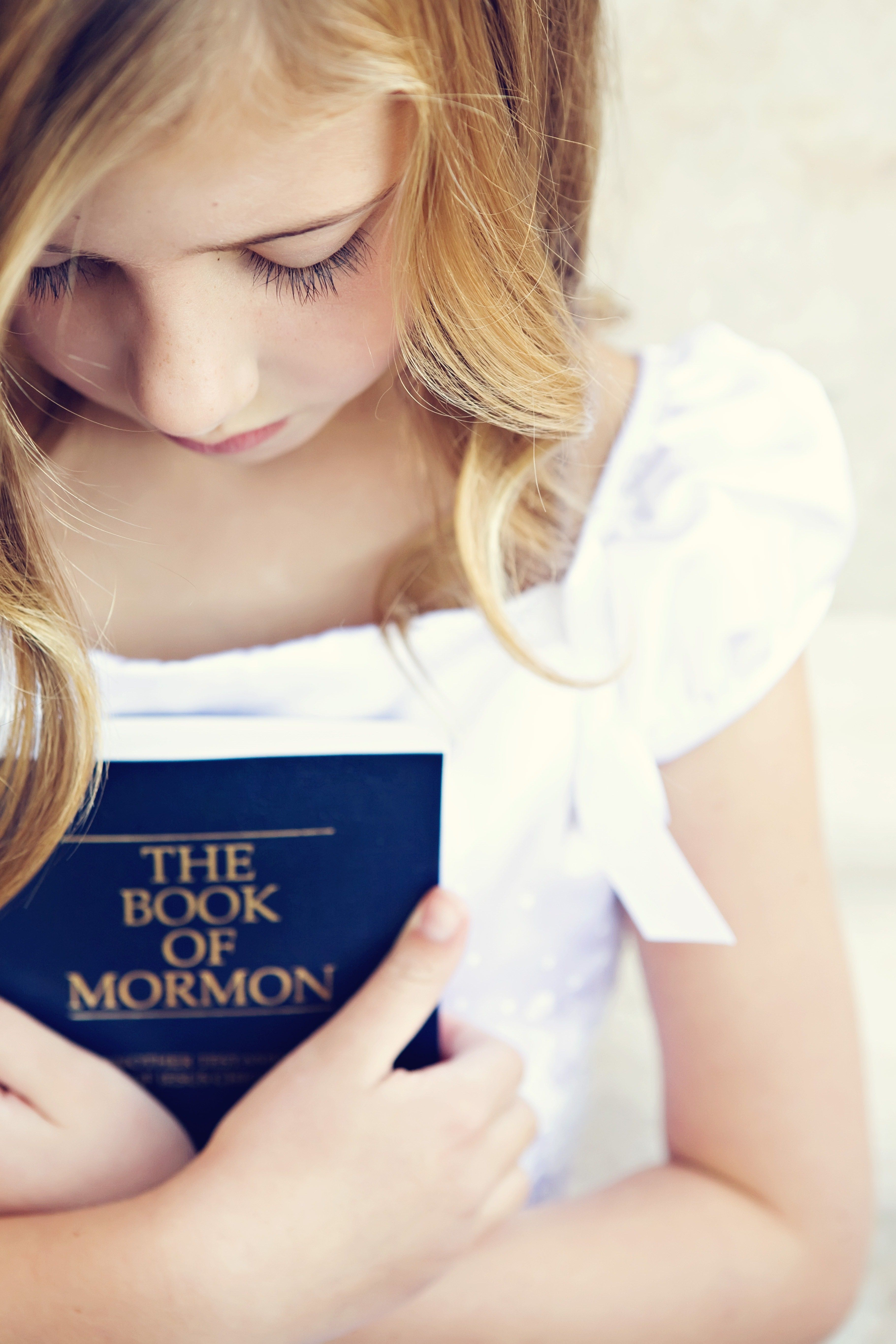 A young girl in a white dress holding a copy of the Book of Mormon.