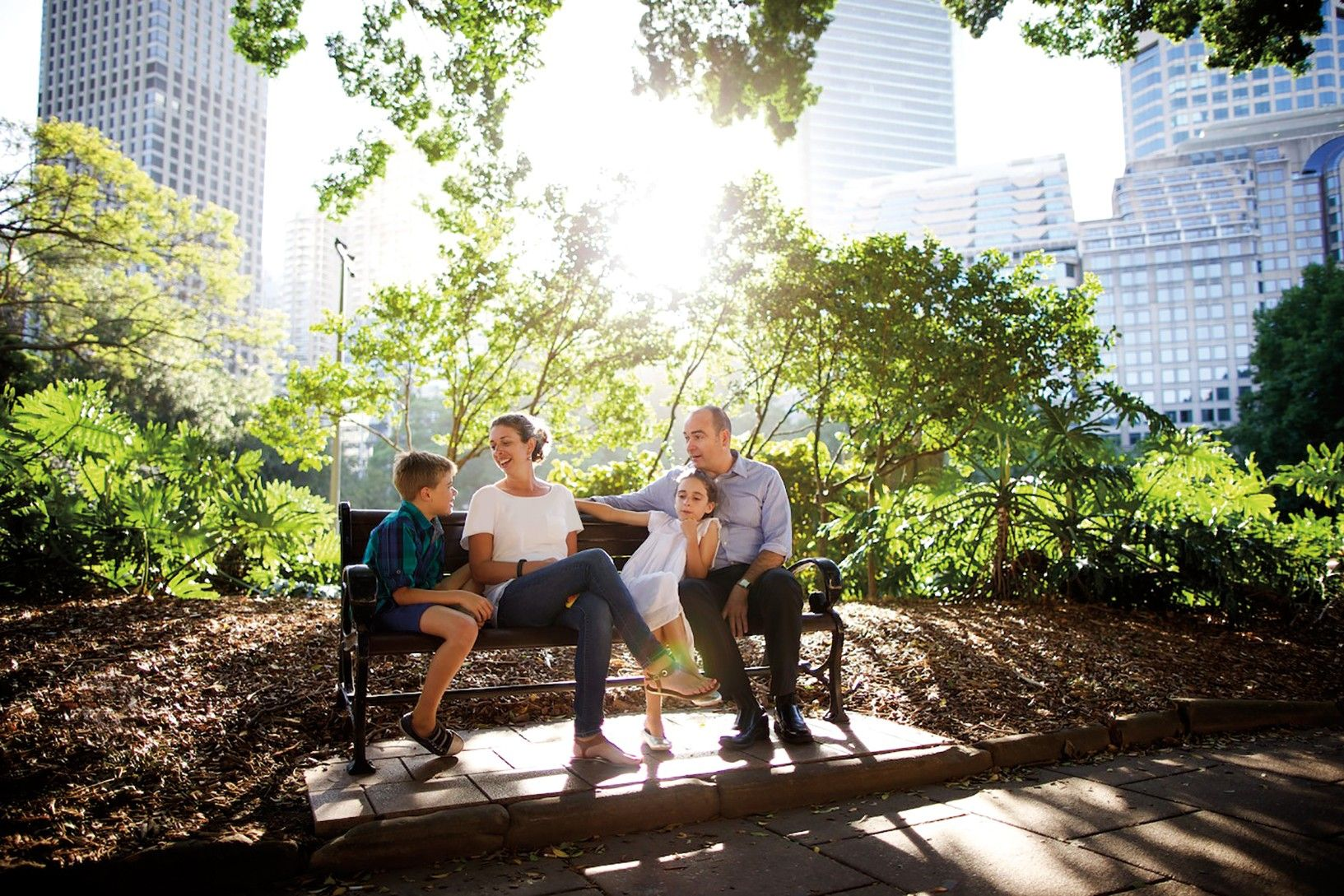 A family in Australia sits together on a park bench.