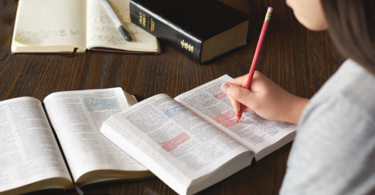 A girl studies the Bible learning about the gospel of Jesus Christ