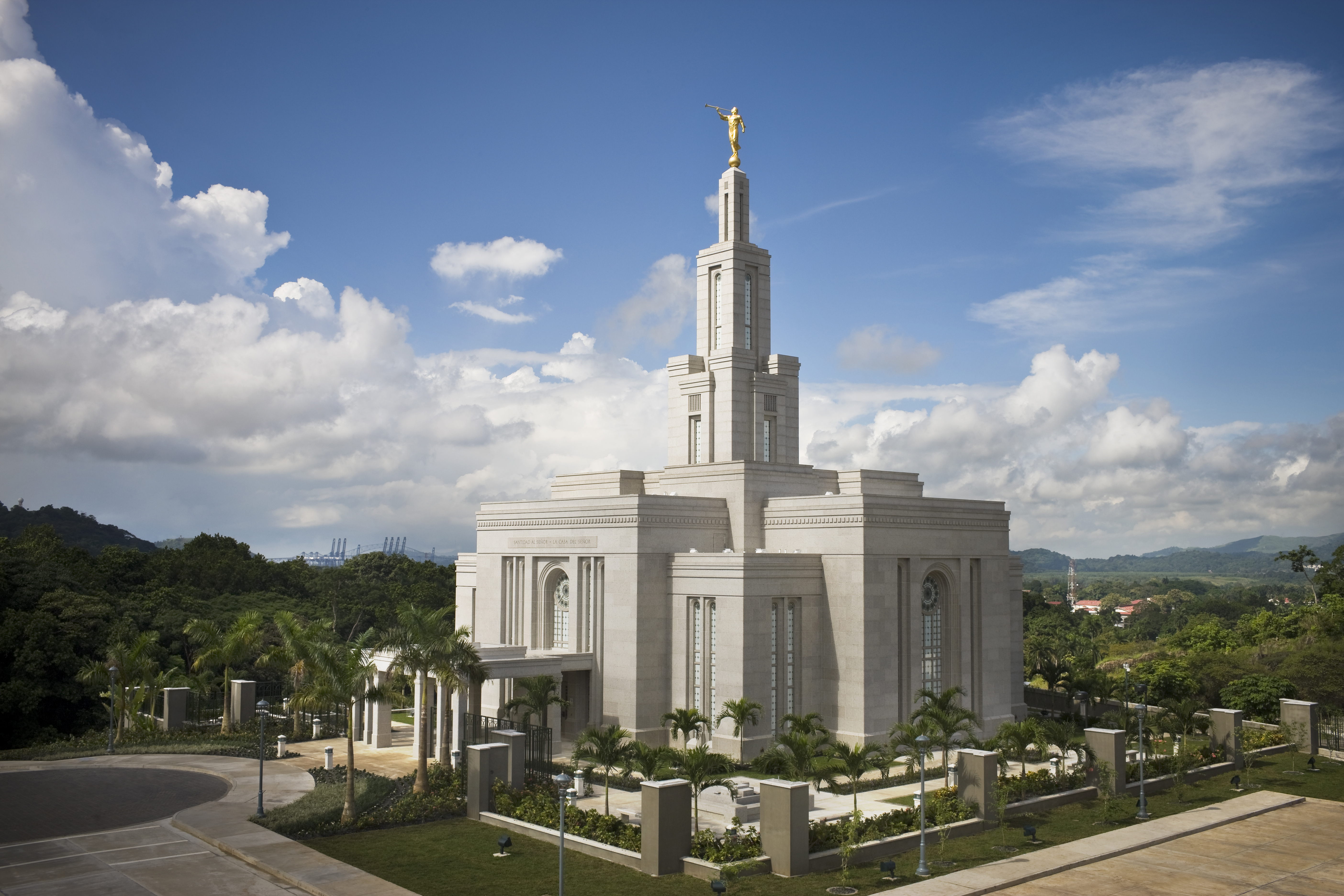 A side view of the Panama City Panama Temple, surrounded by palm trees, with large white clouds overhead.
