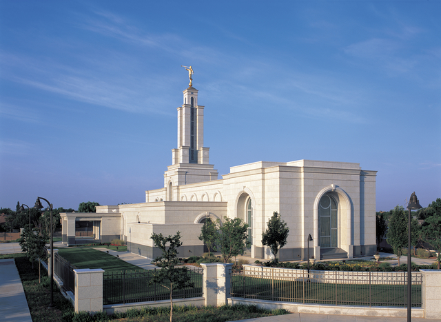 A view of the Lubbock Texas Temple from afar, with a black fence surrounding the grounds.