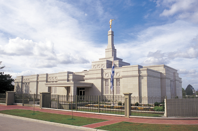 The sun lights up the flag, fences, and exterior walls of the Montevideo Uruguay Temple.