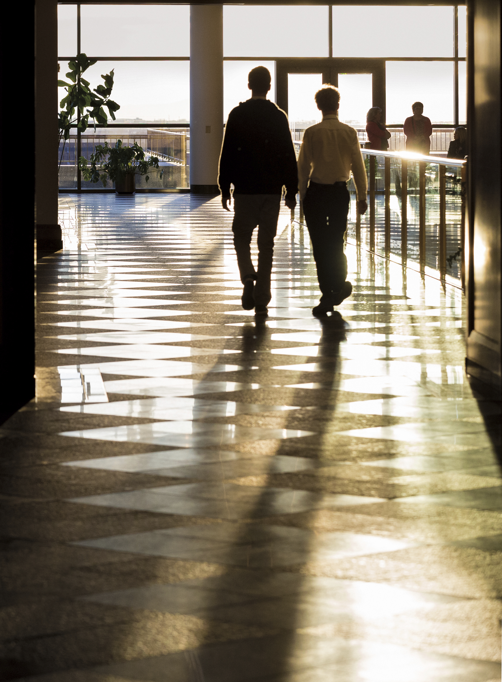 Two young men walking inside the Conference Center.