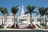 The front of the Kona Hawaii Temple, with a row of palm trees and beds of bright red flowers in the foreground.