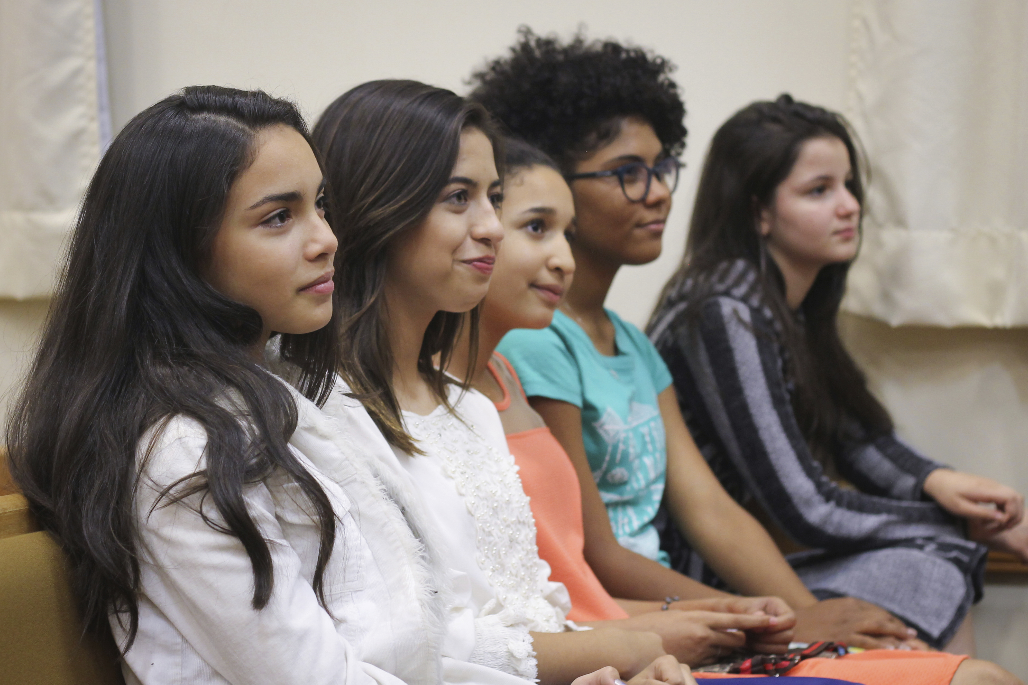 A row of young women watching the broadcast of the general women's session at their local meetinghouse in Brazil.