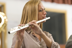 A young woman with long blonde hair stands and plays the flute with people on either side of her playing as well.
