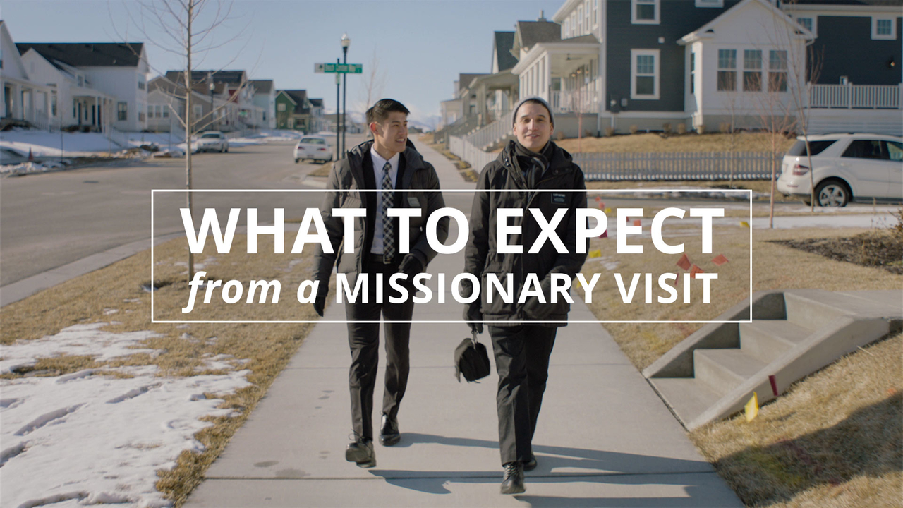 Two elder missionaries walk down a suburban street looking to teach people about the Book of Mormon