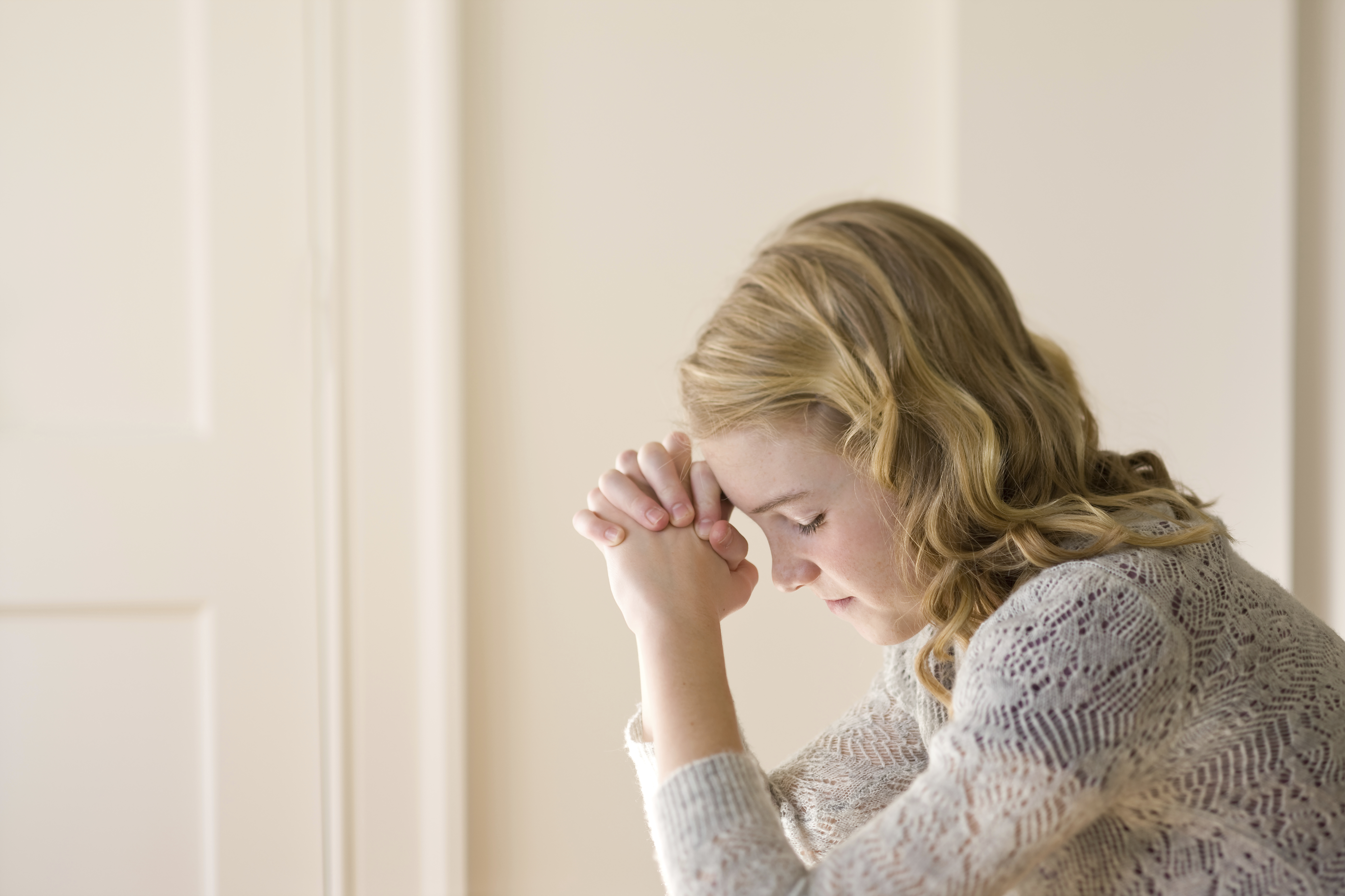 A young woman kneels in prayer.