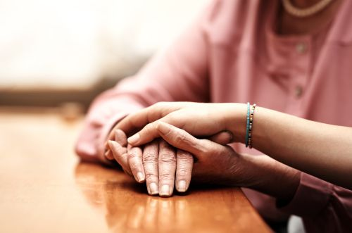 two person's hands comforting each other