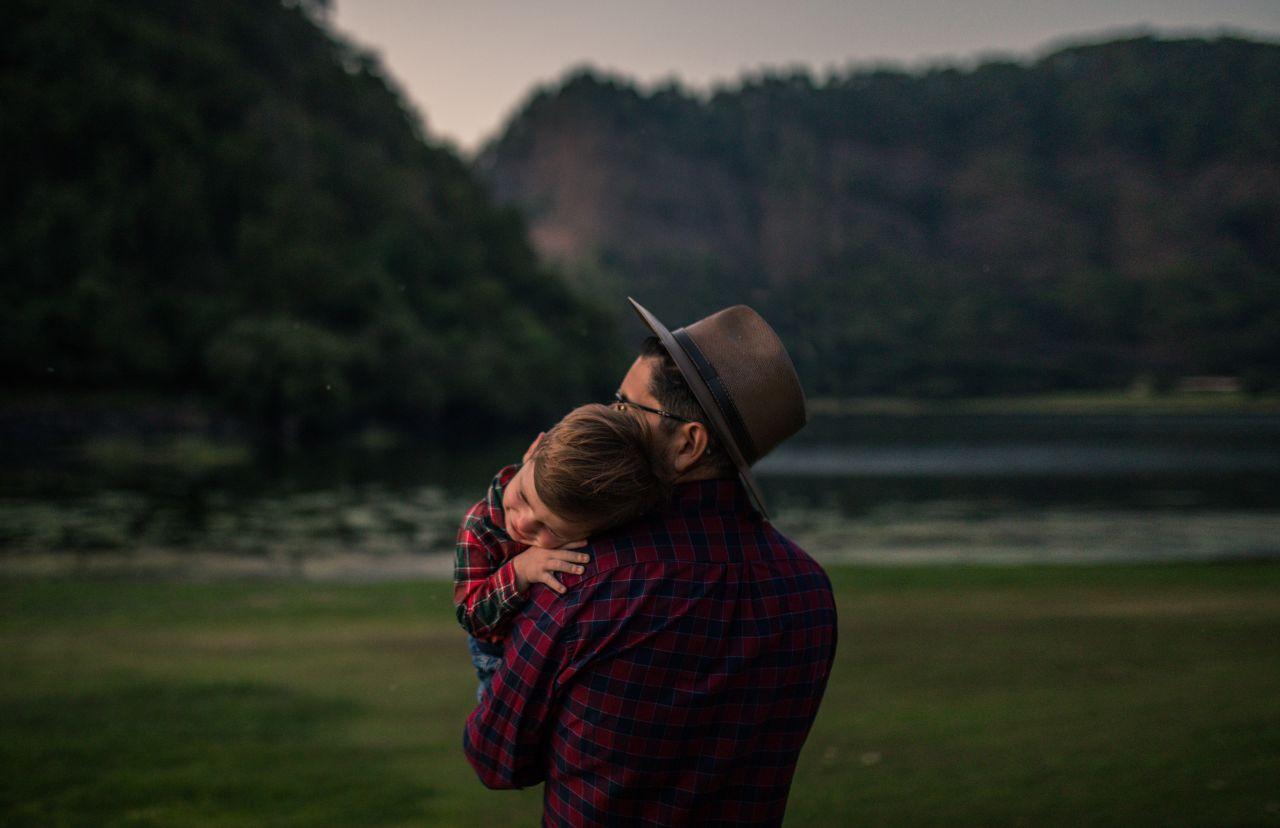Un padre sostiene amorosamente a su hijo pequeño mientras disfrutan de la naturaleza