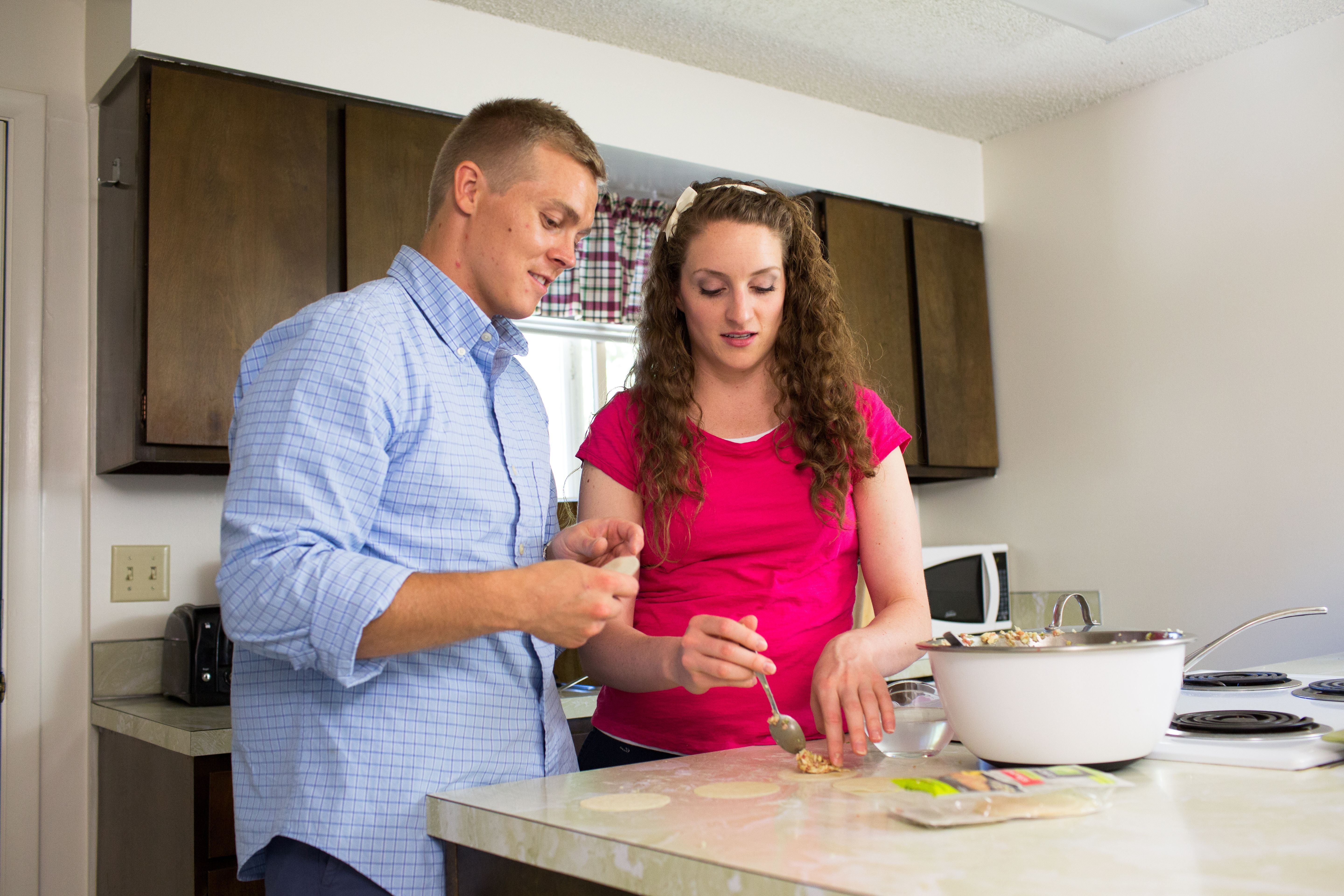 A couple preparing food together in the kitchen.