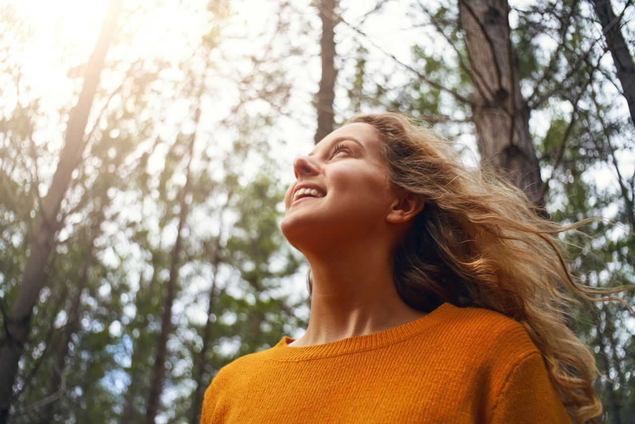 A young woman smiling enjoys time in the sunshine of a forest