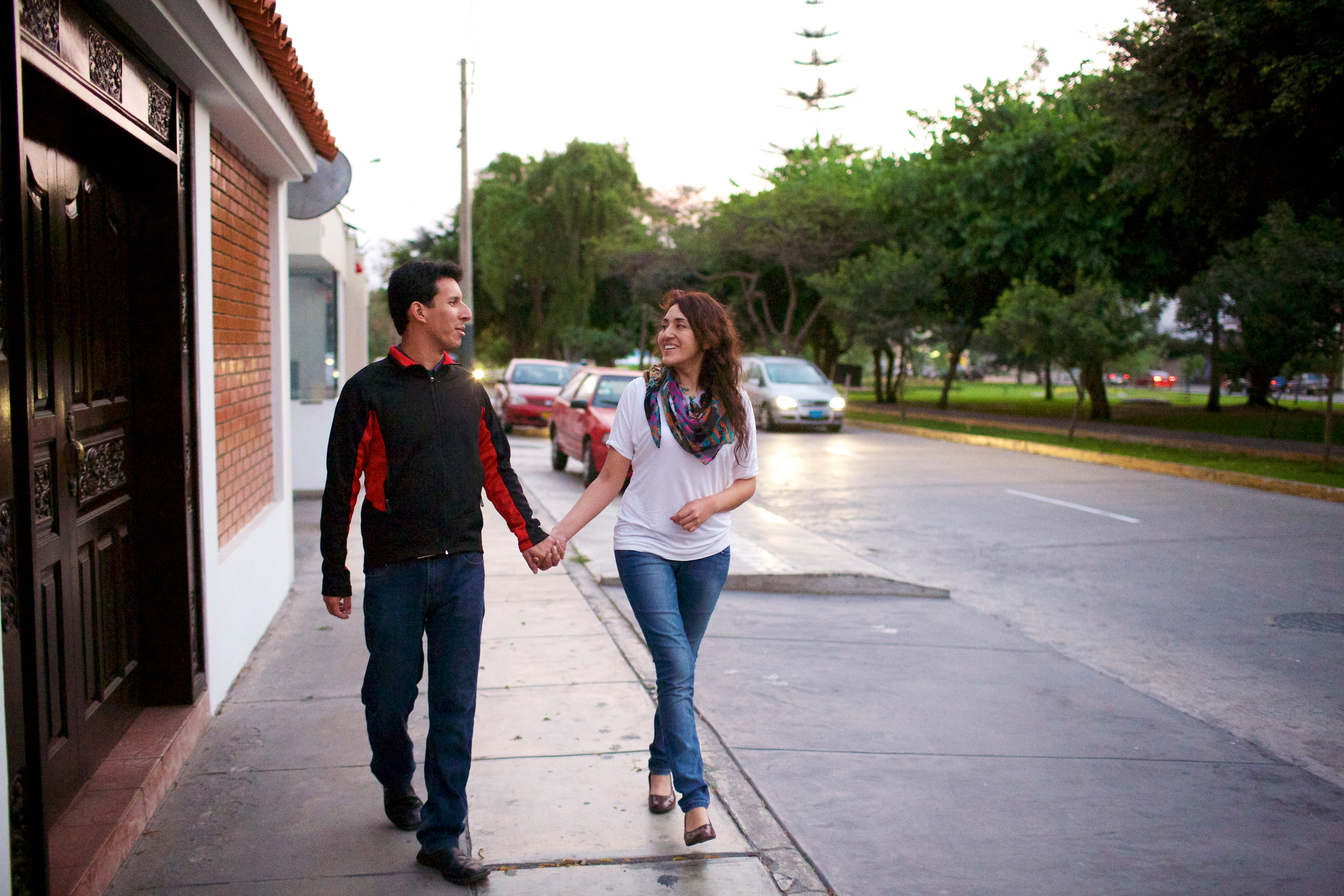 A husband and wife holding hands and walking down a sidewalk.