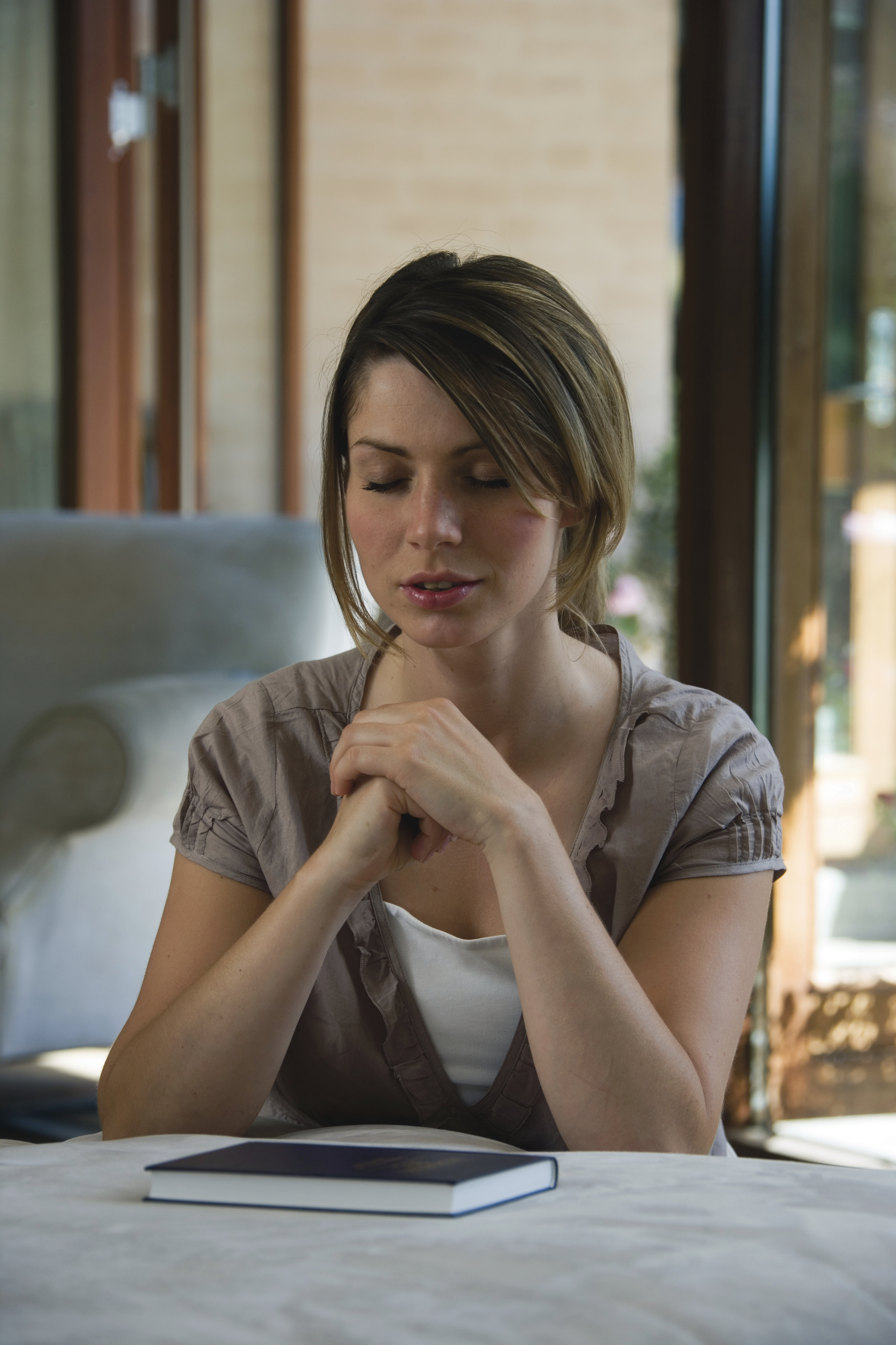 A woman prays during scripture study.