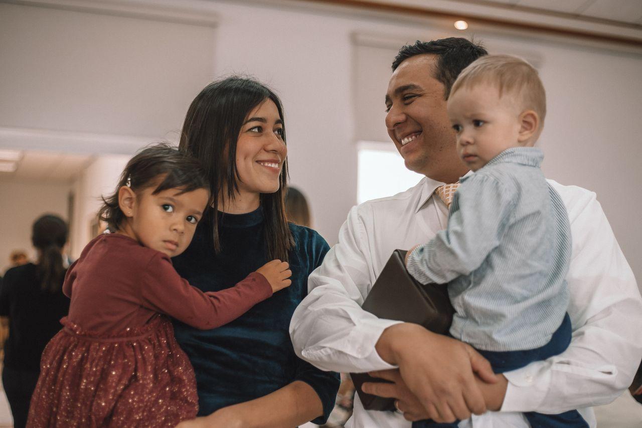 Una pareja casada se sonríe mientras llevan a sus hijos a la capilla