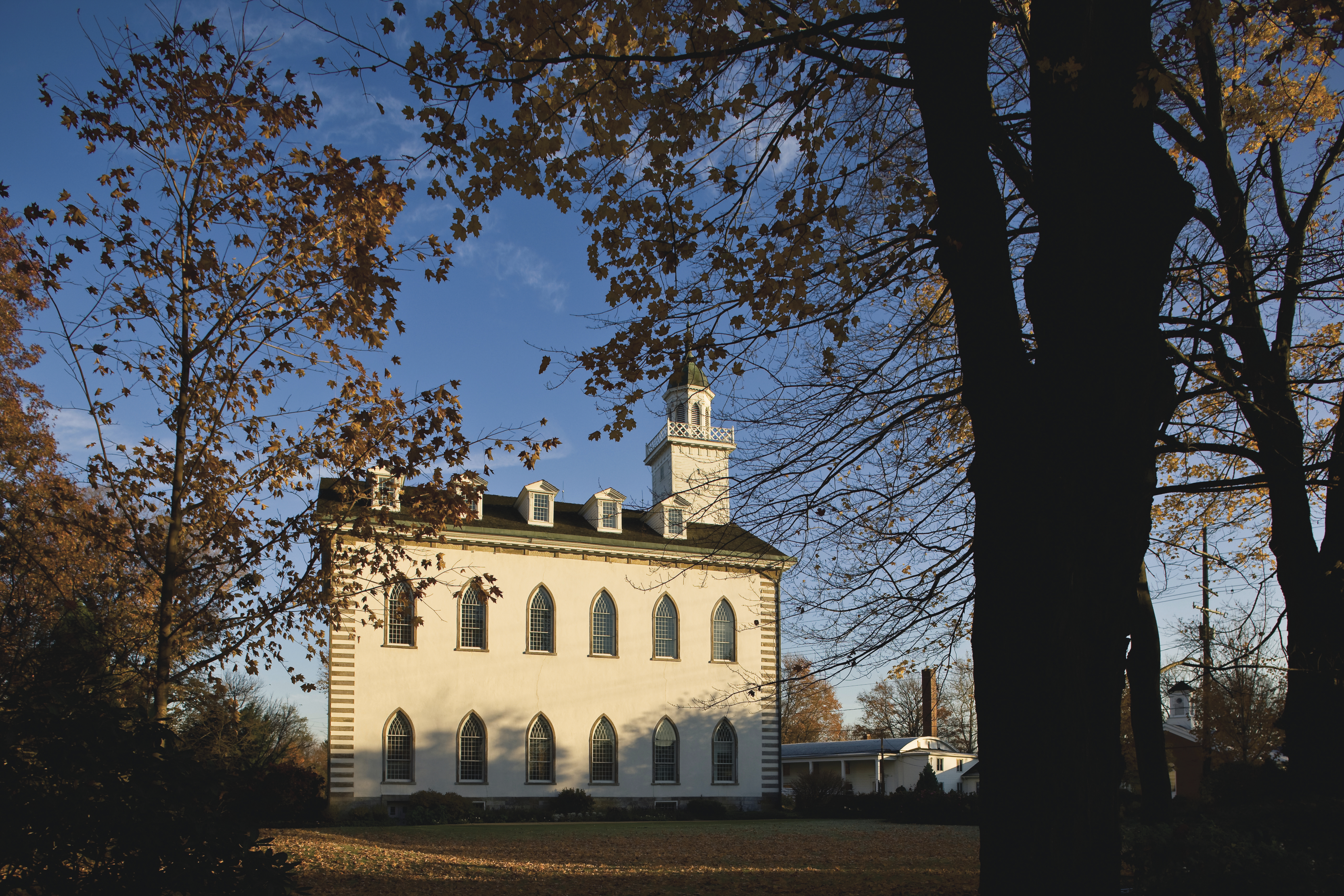 A side view of the Kirtland Temple in the fall, including scenery.
