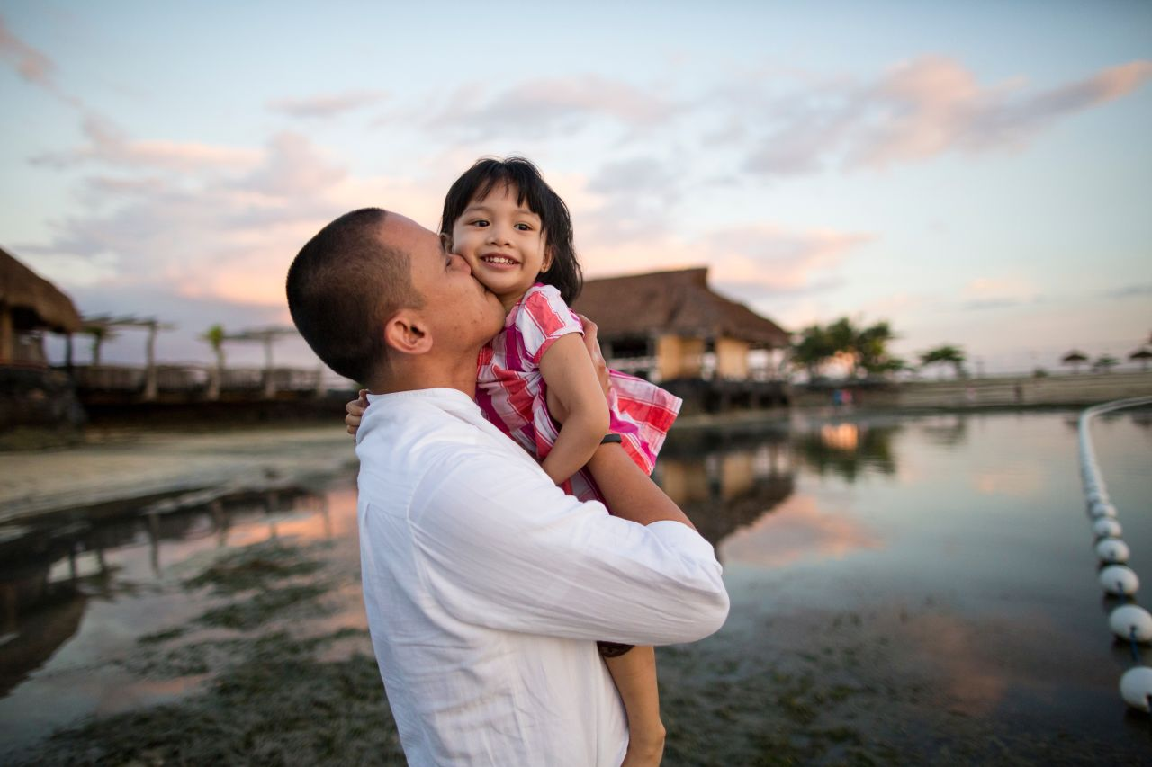 A father holds his young daughter at a beach