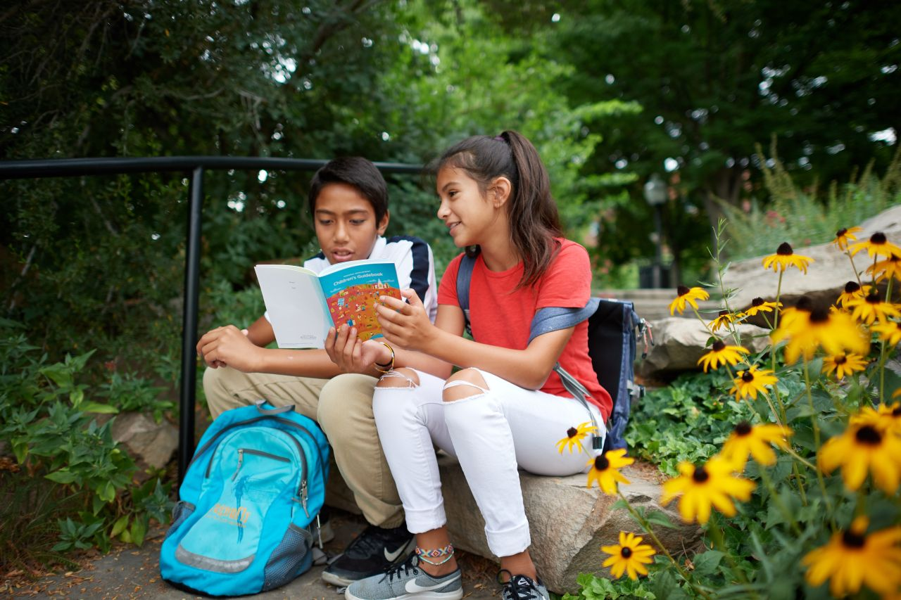 Young man and young woman reading booklet outside