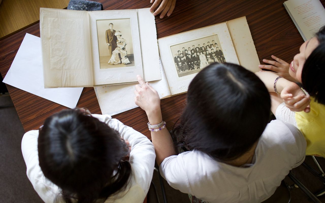 Three woman look through old foto albums at a kitchen table going through their family history