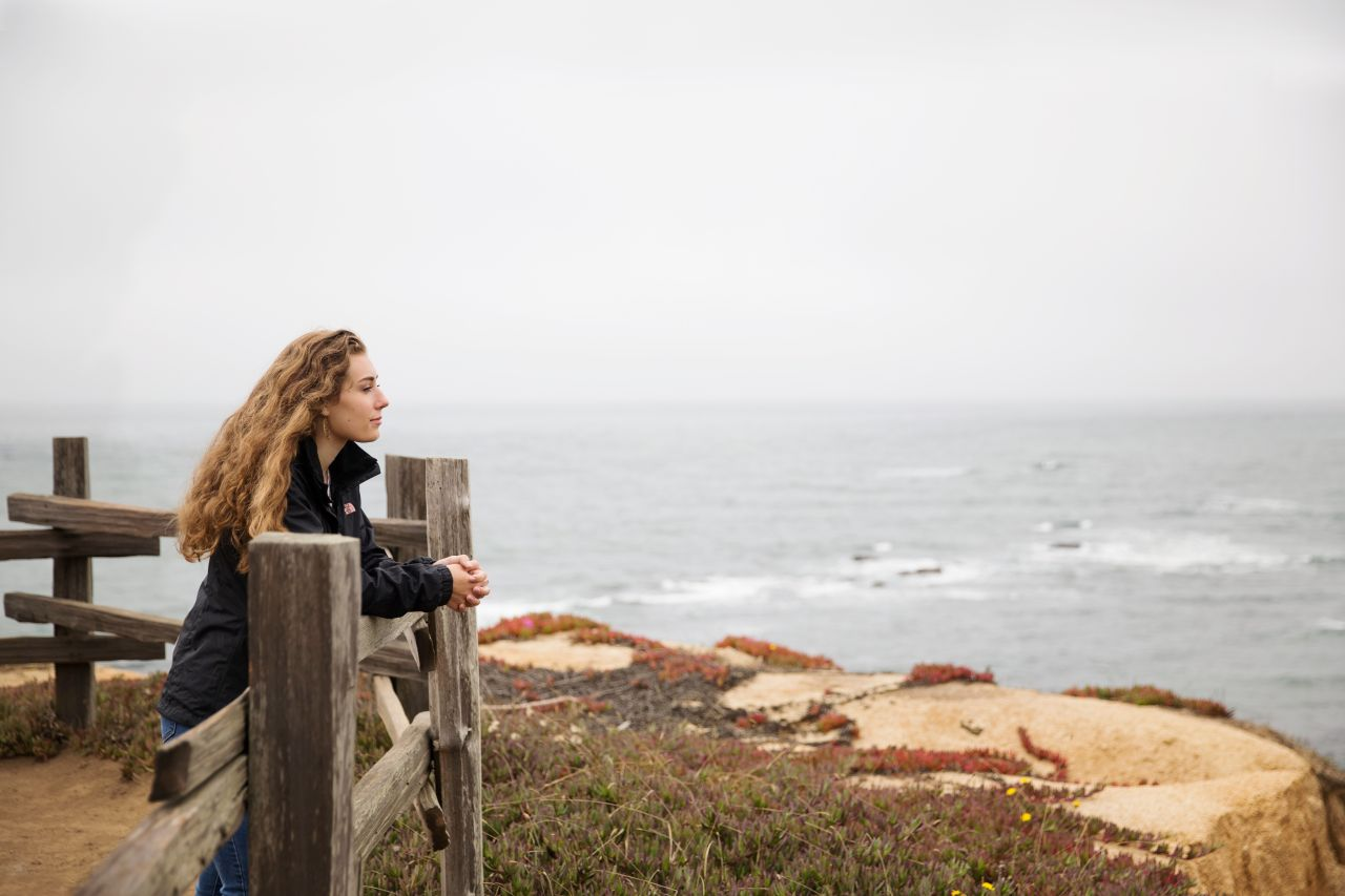 A woman leans on a railing above the seaside contemplating the gospel of Jesus Christ