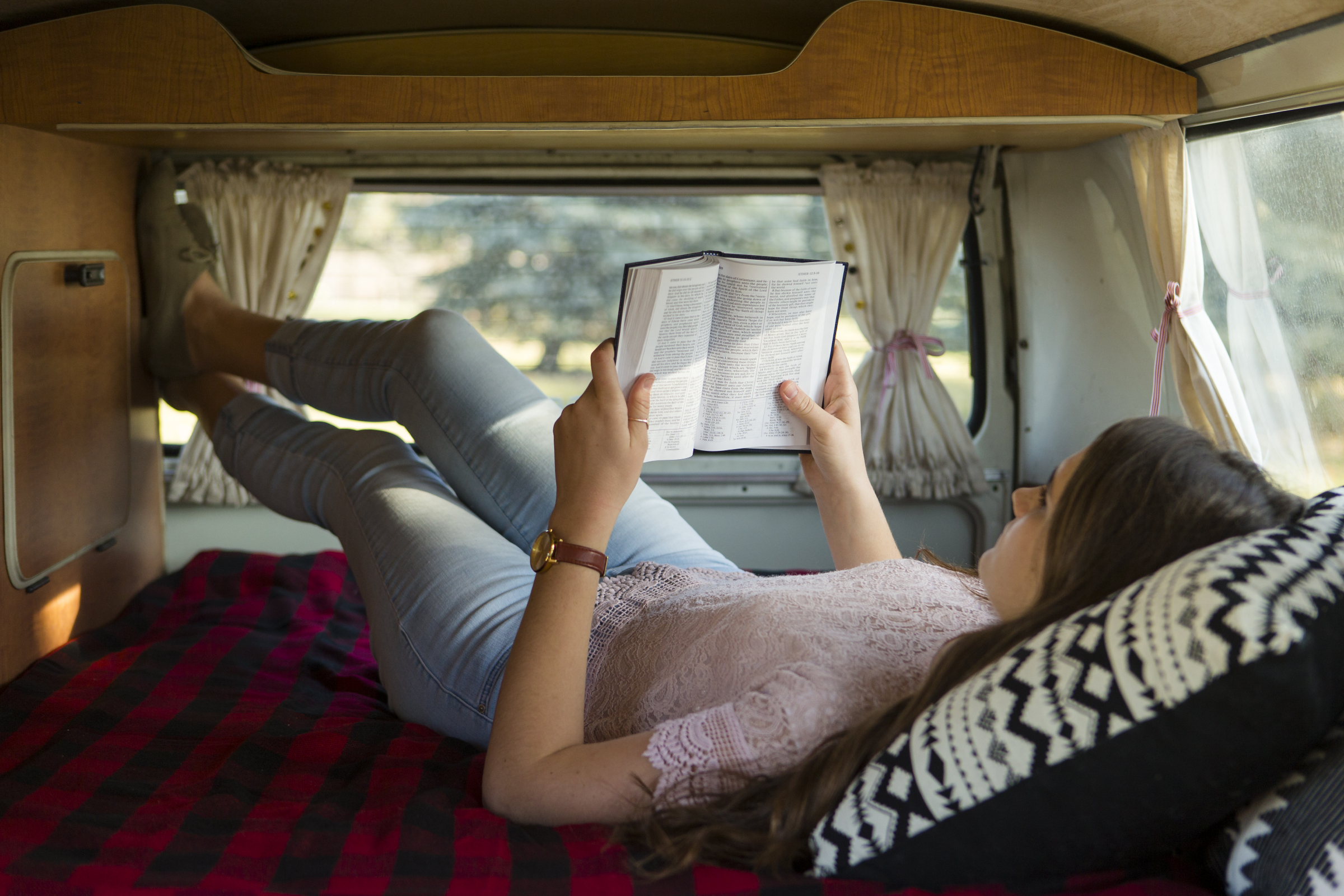 A woman lays on a bed in a camper and reading the Bible learning about faith