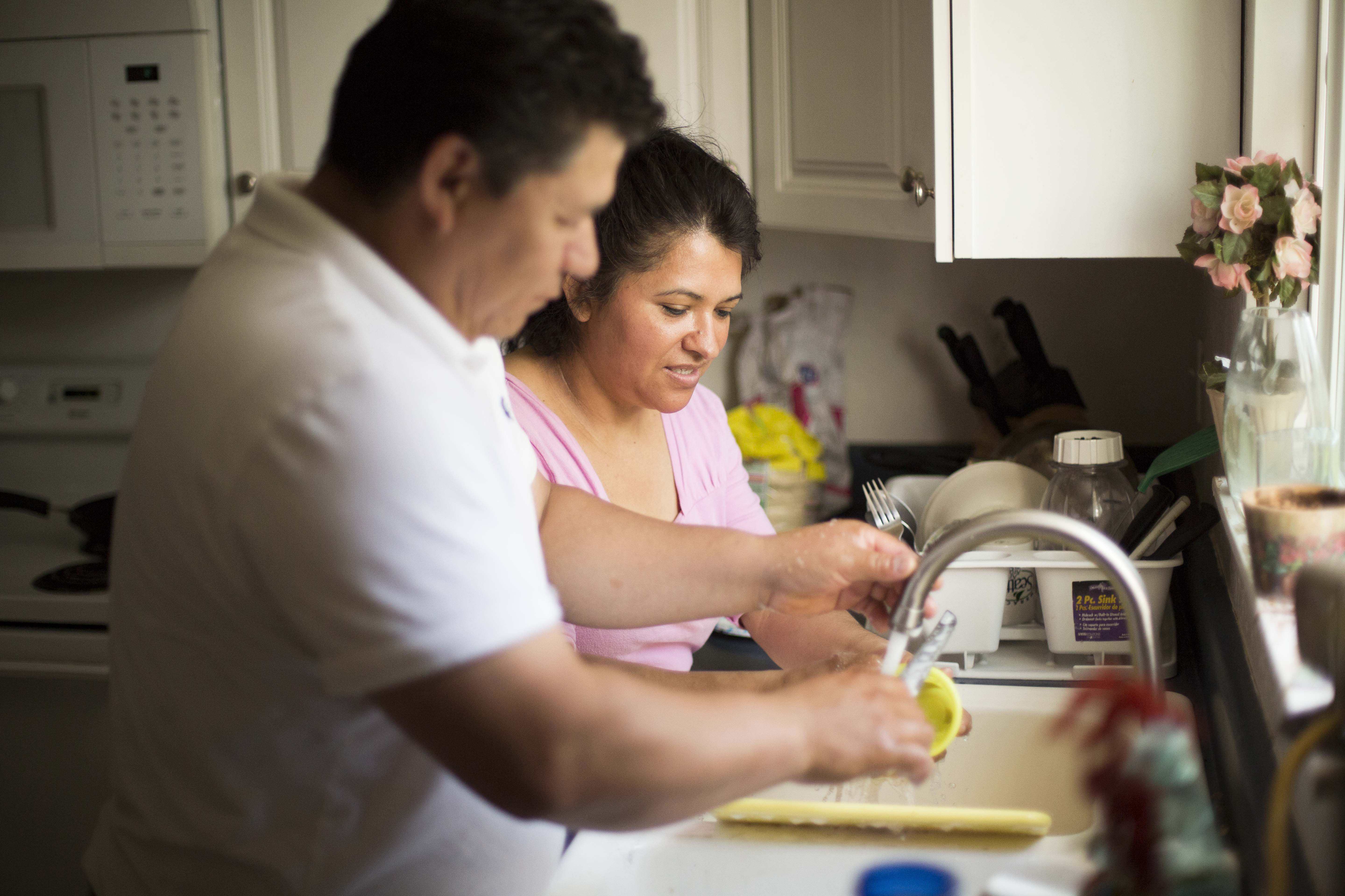 A husband and wife stand by their kitchen sink and wash dishes together.