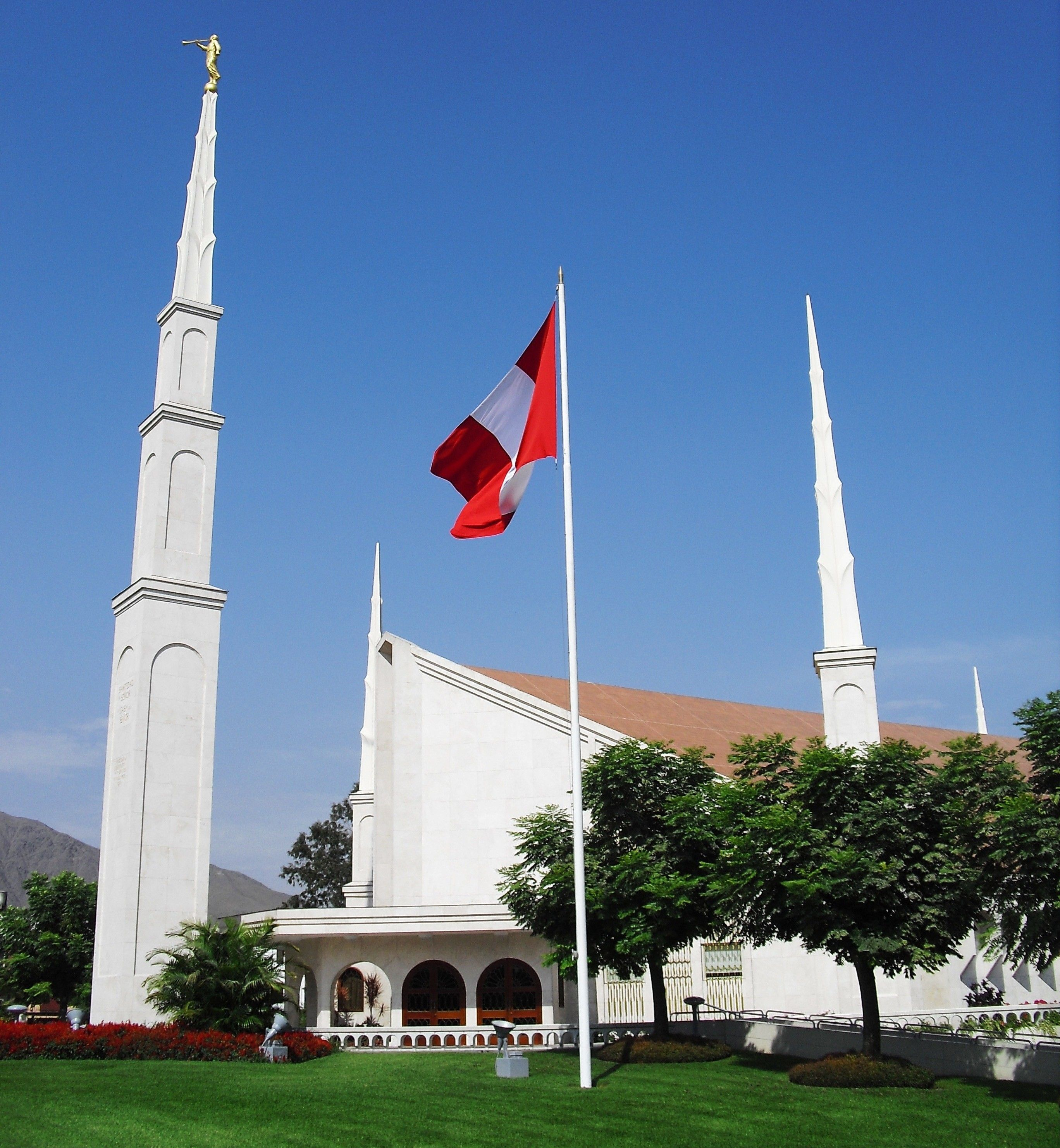 The Lima Peru Temple spires, including the entrance, scenery, and flag.