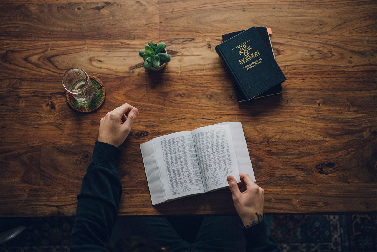 A man studies the Bible and the Book of Mormon at his kitchen table