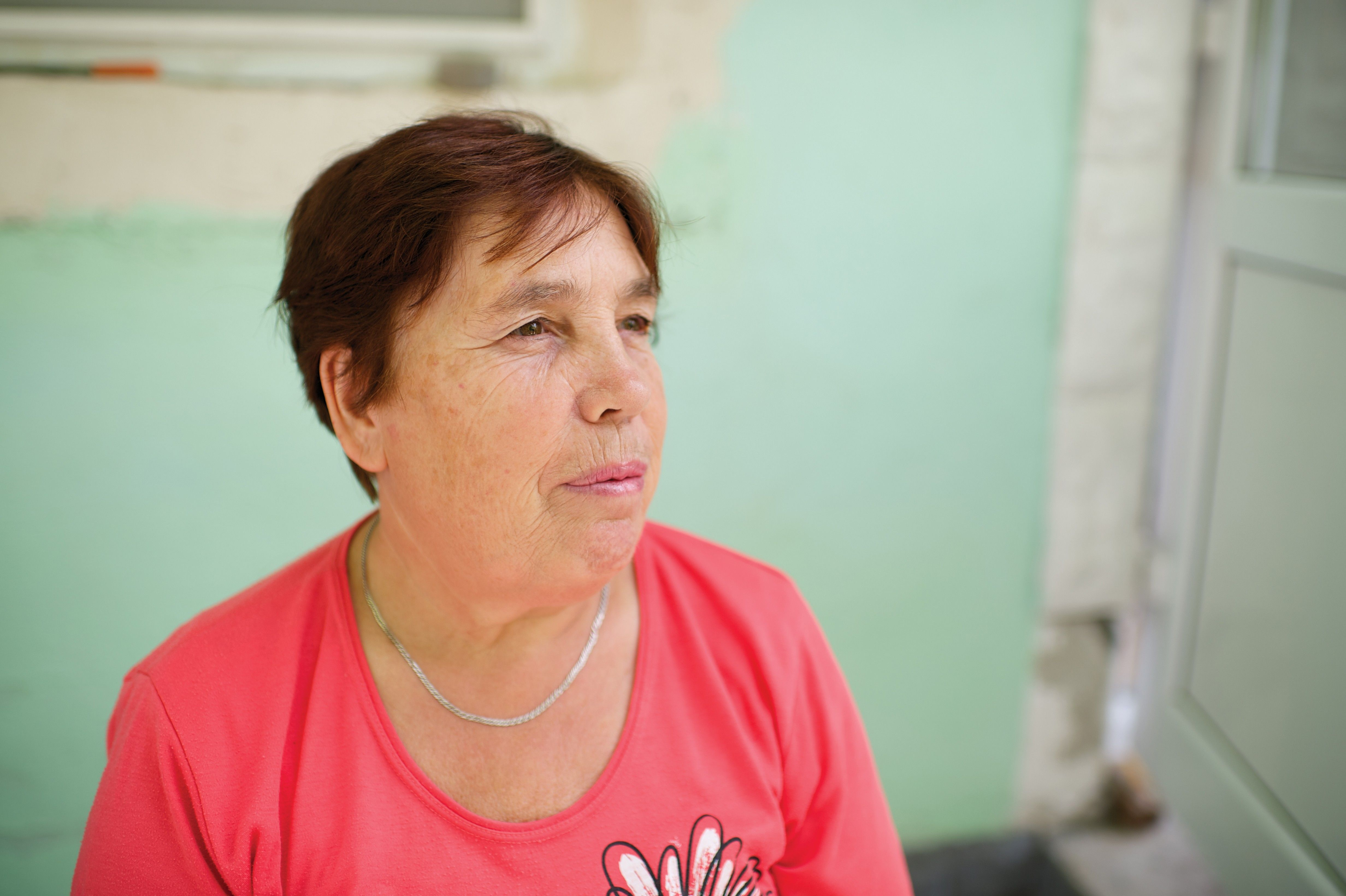 An informal portrait of a woman sitting outside in Romania.