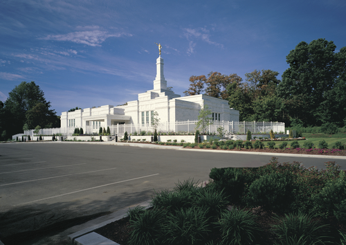A view of the Louisville Kentucky Temple from across the parking lot, behind a white fence.