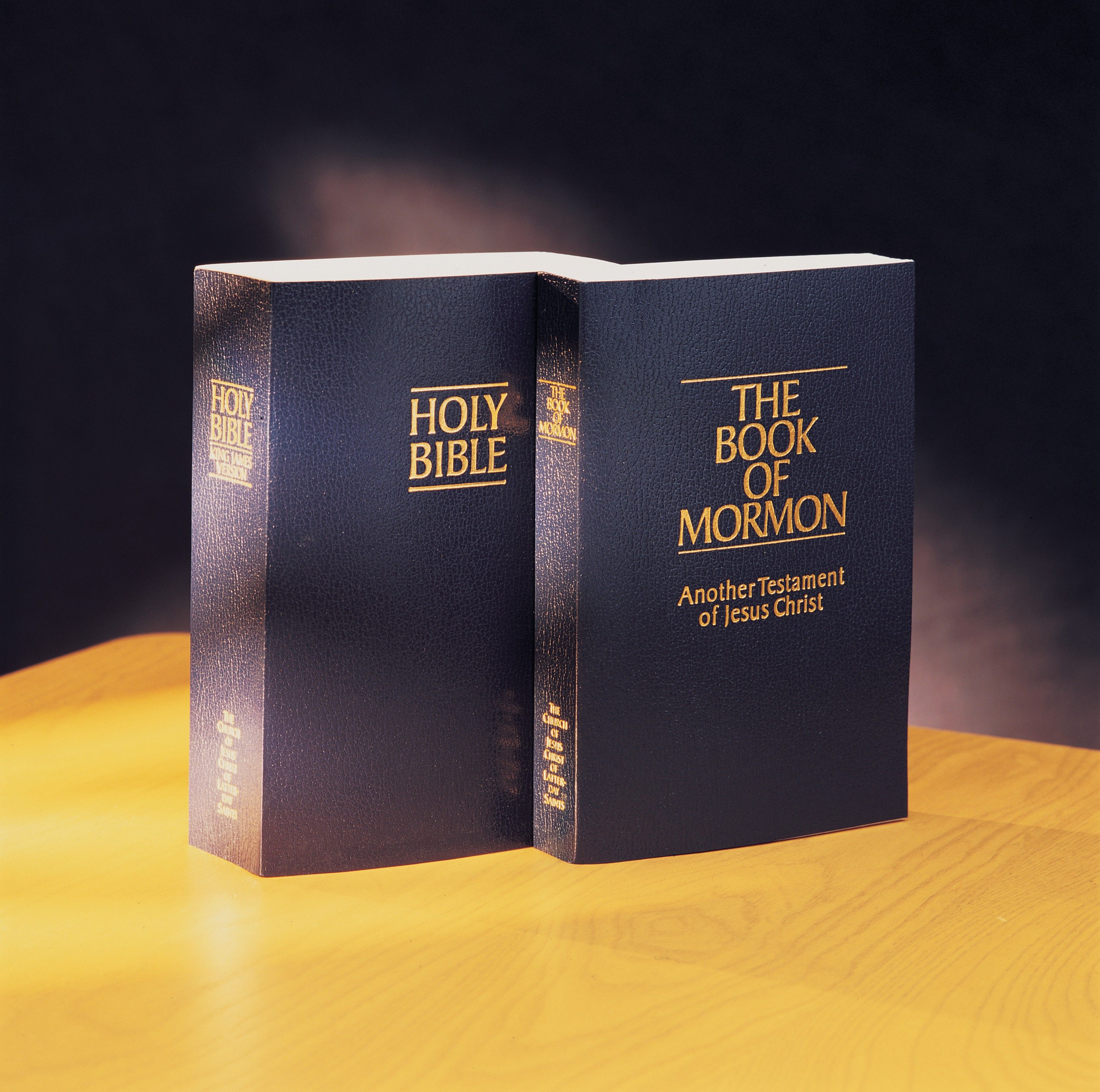 A Bible and a Book of Mormon on a table.