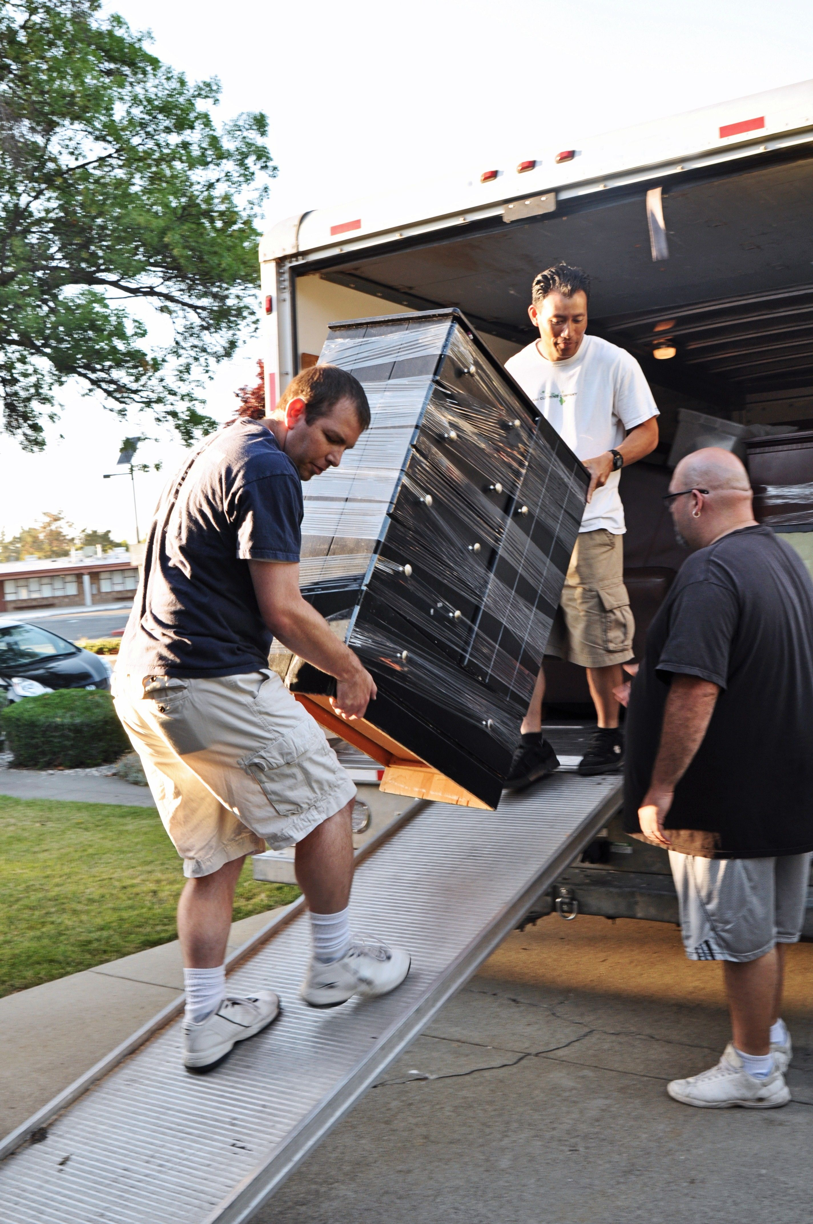 Two men carry a dresser out of a moving truck.