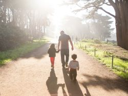 A father and his children walk down a park path
