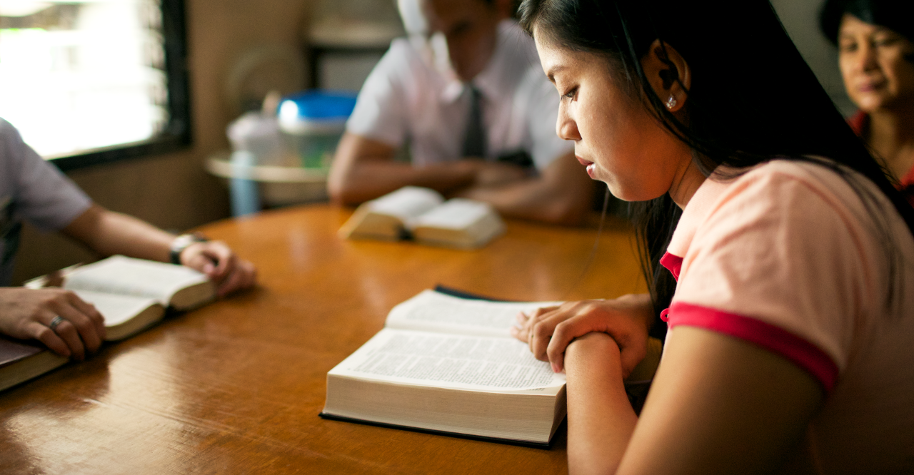 The Book of Mormon is studied by a family at their kitchen table while they are taught by the missionaries