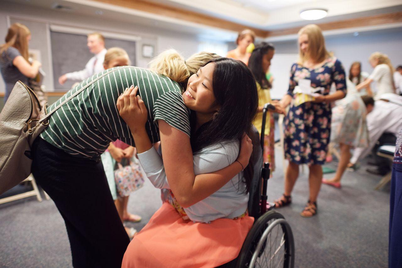 Una joven en silla de ruedas está hablando con otras mujeres jóvenes y recibe un abrazo